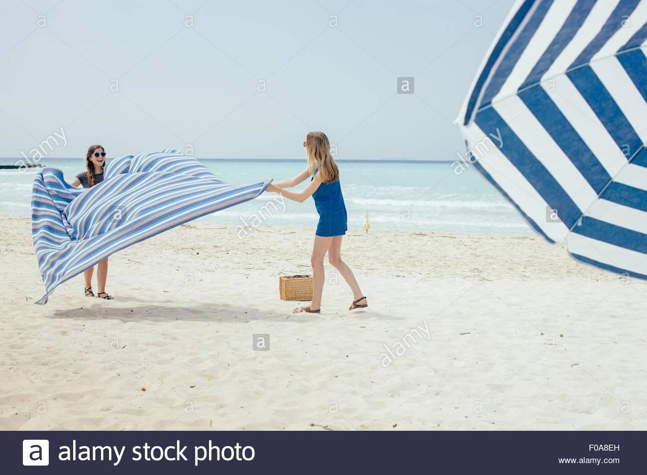 Deux jeunes amis féminins pose couverture de pique-nique sur la plage Photo Stock