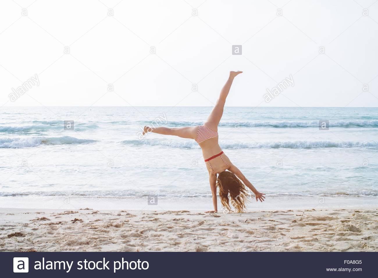 Young woman wearing bikini cartwheeling on beach Photo Stock