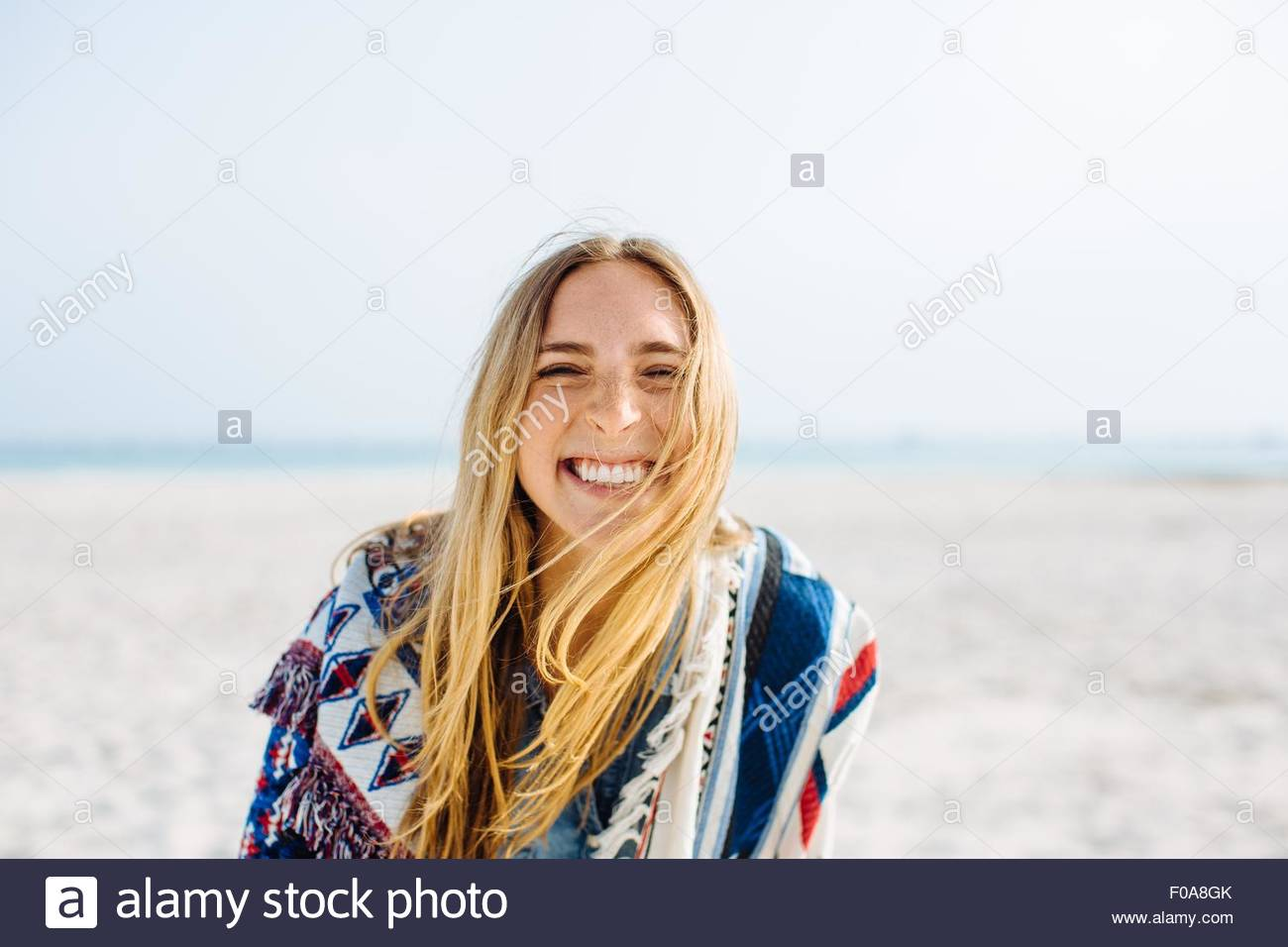 Portrait of young woman wrapped in blanket faisant sourire on beach Photo Stock