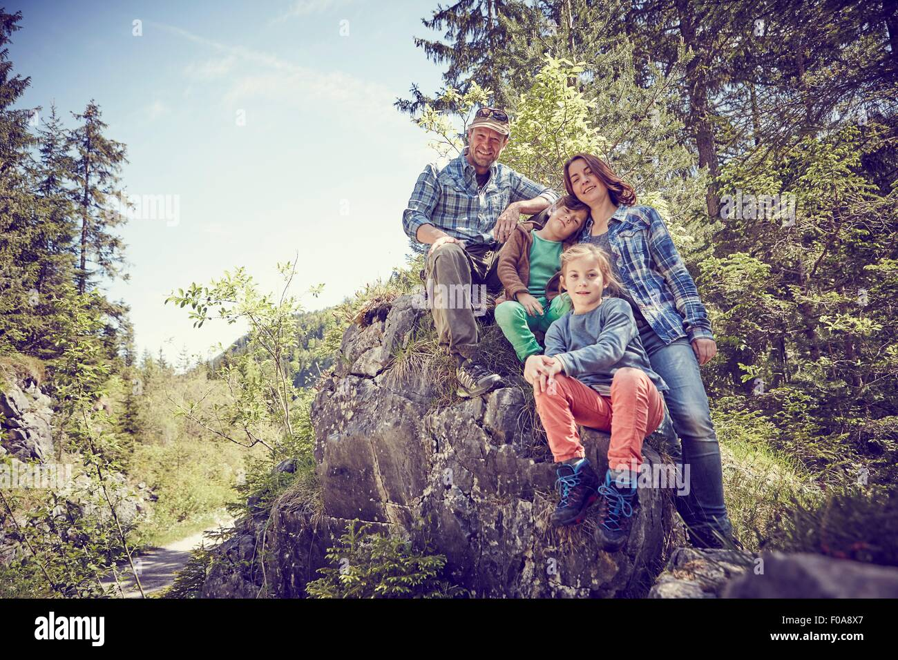 Portrait of family sitting on rock in forest Photo Stock