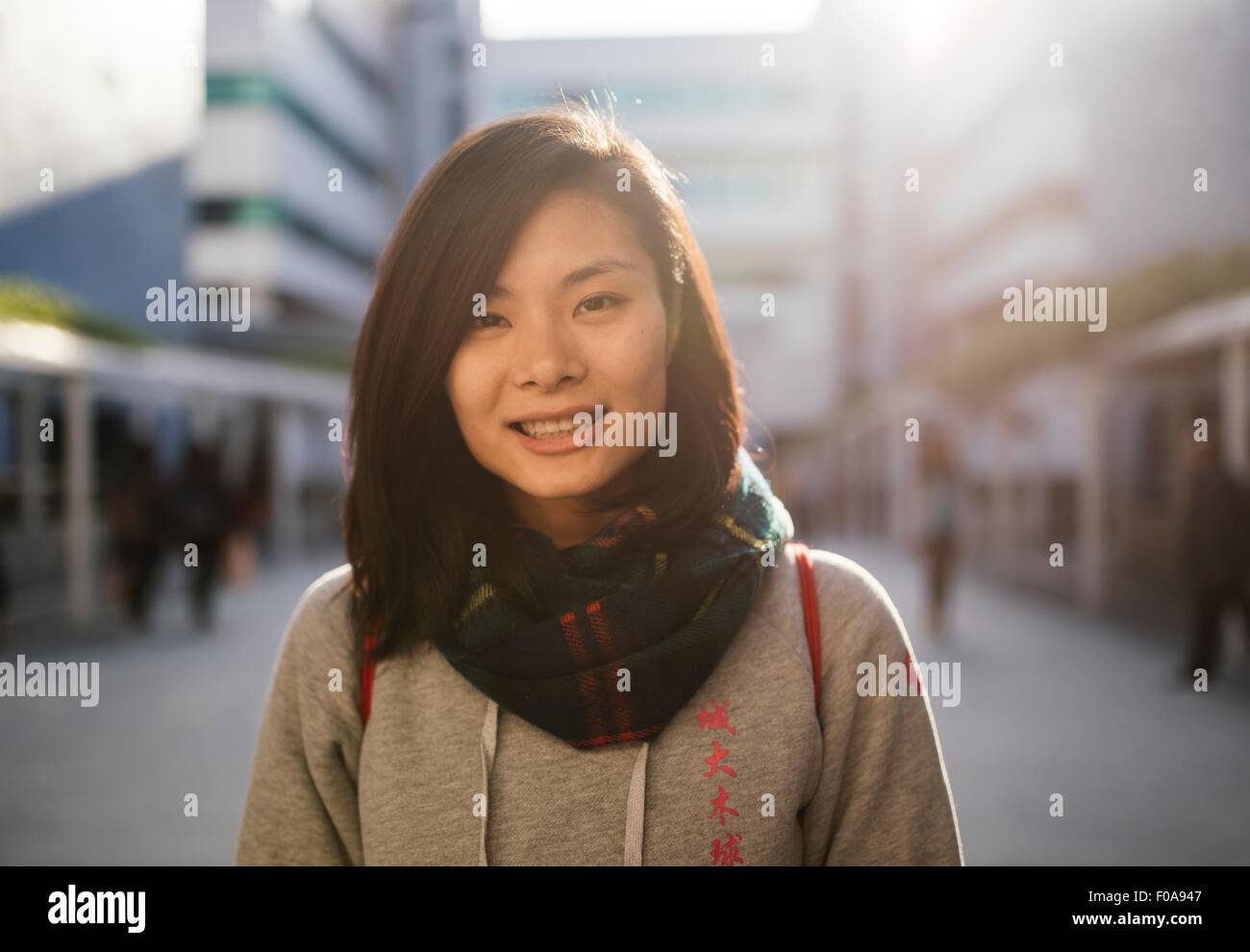 Portrait of young woman wearing hooded top et écharpe, smiling at camera Photo Stock