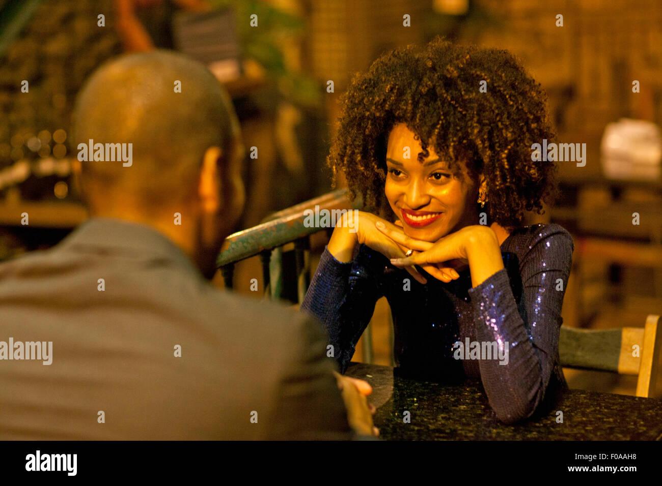 Couple assis à table au bar, face à face Banque D'Images