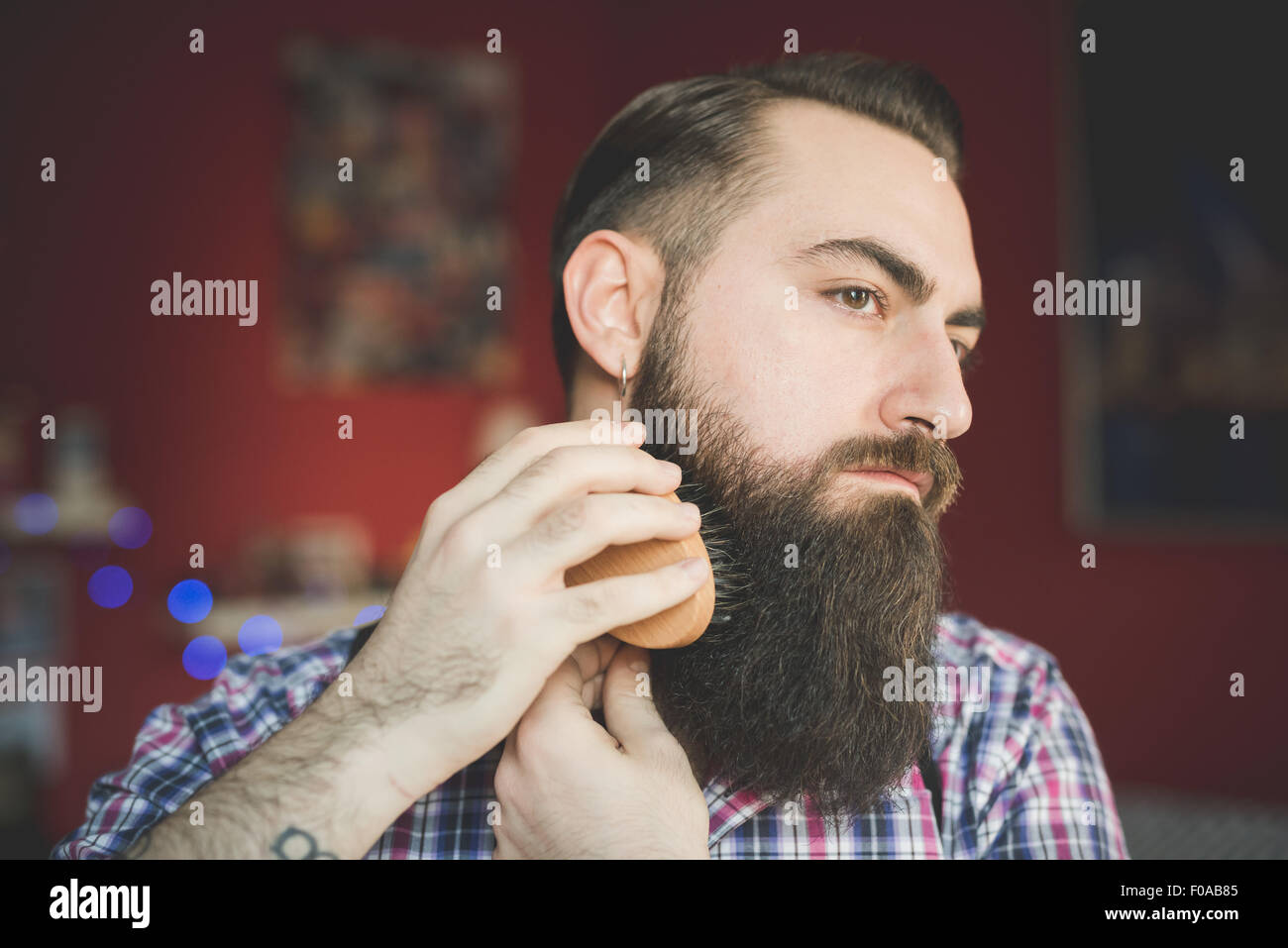 Jeune homme barbu, sa barbe de brossage Photo Stock