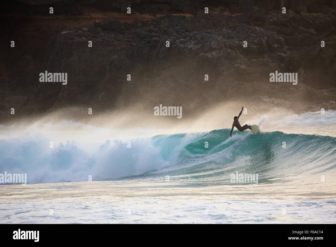 La silhouette du jeune homme vague de surf au coucher du soleil, Fuerteventura, Espagne Photo Stock