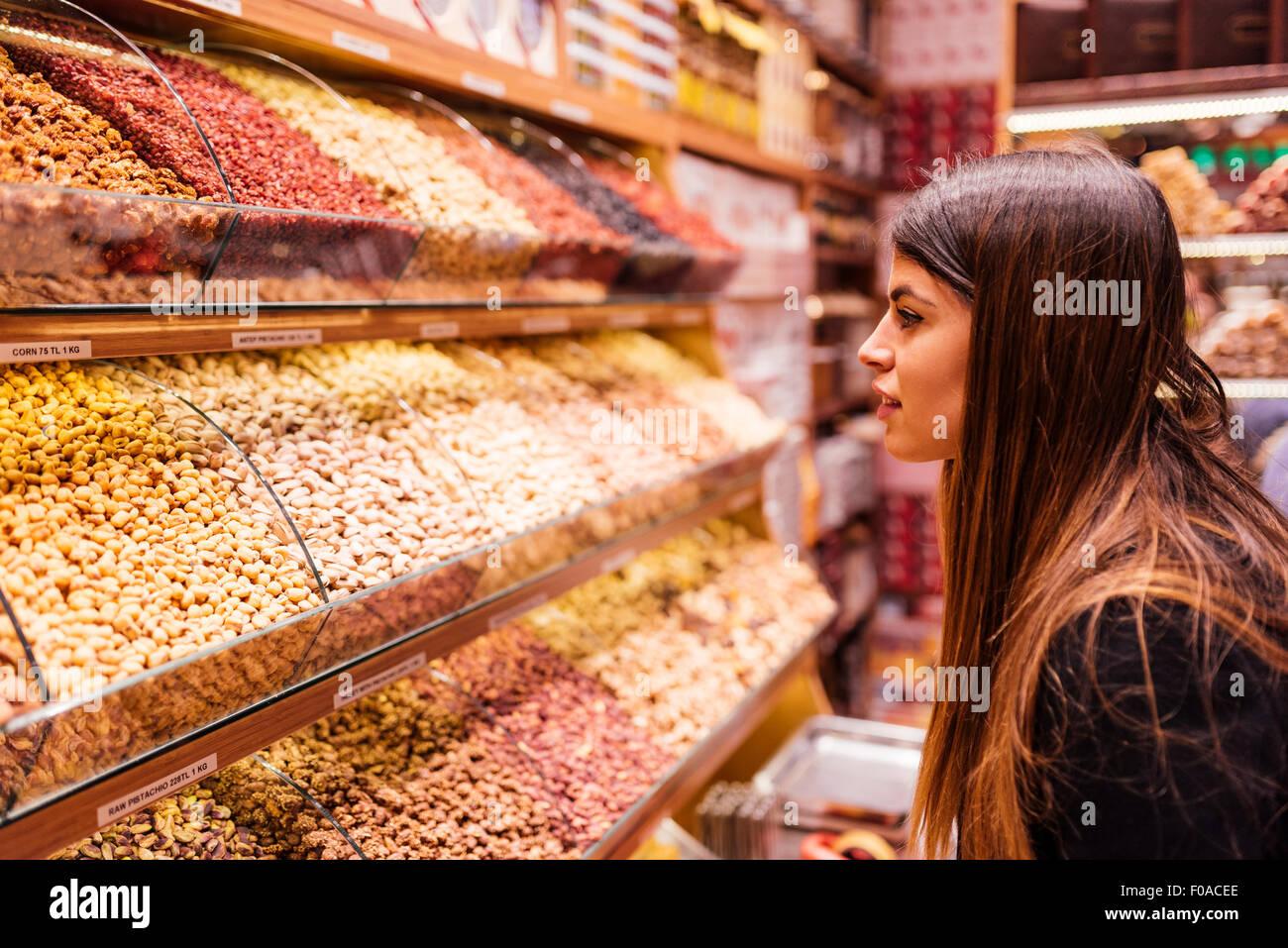 Jeune femme à la recherche dans les aliments au marché, Istanbul, Turquie Photo Stock