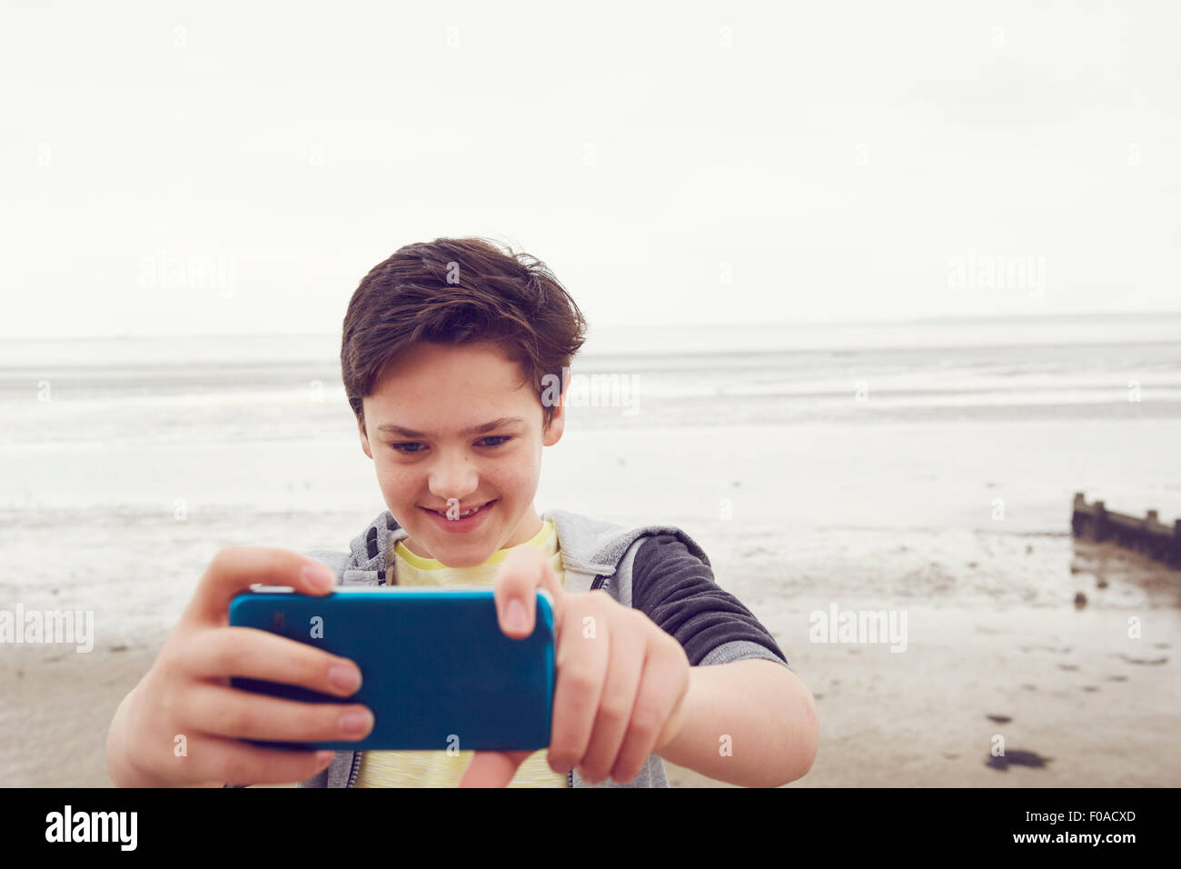 Smiling teenage boy taking selfies smartphone à seaside, Southend on Sea, Essex, UK Photo Stock