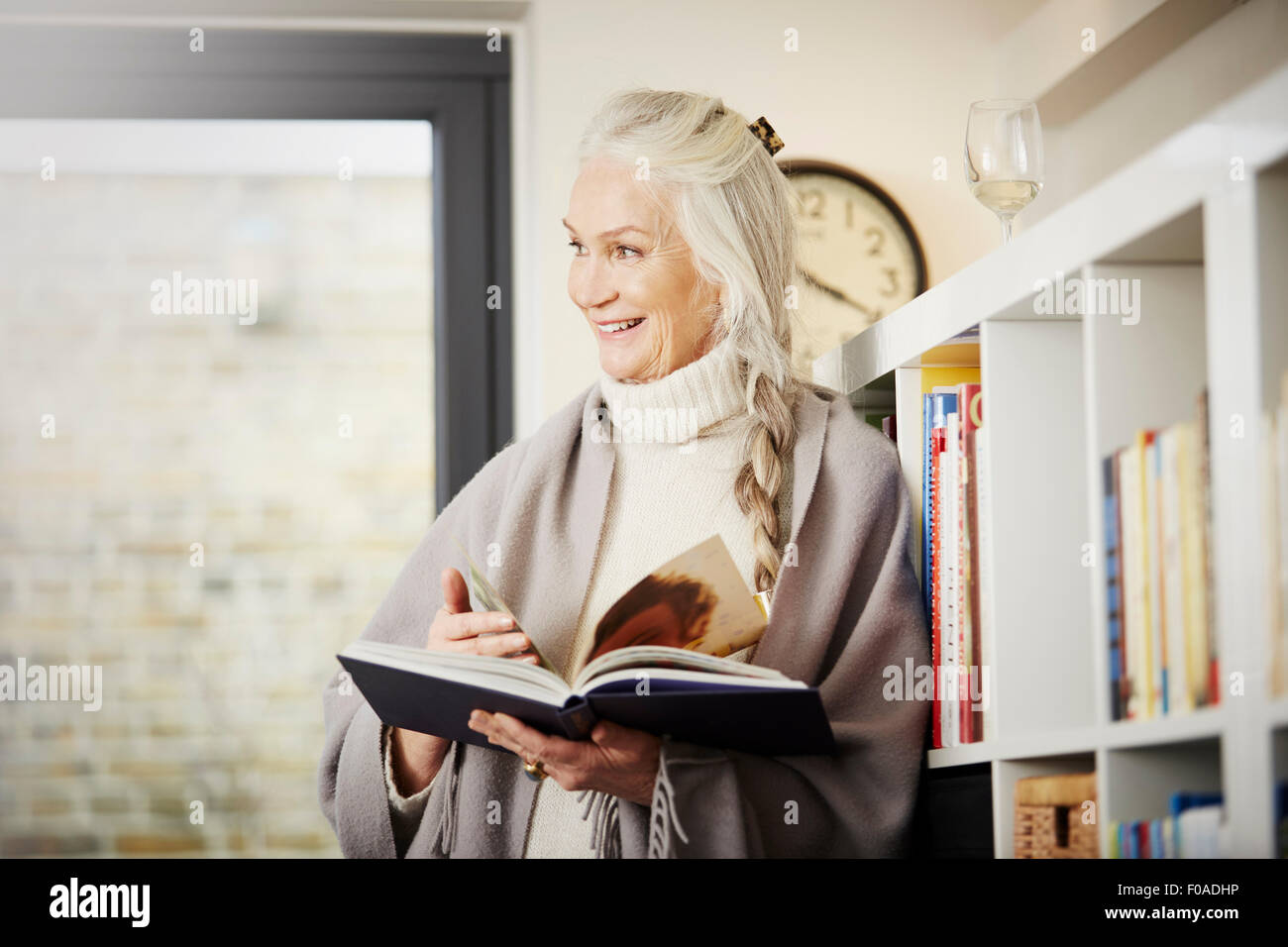Senior woman reading book at home Photo Stock