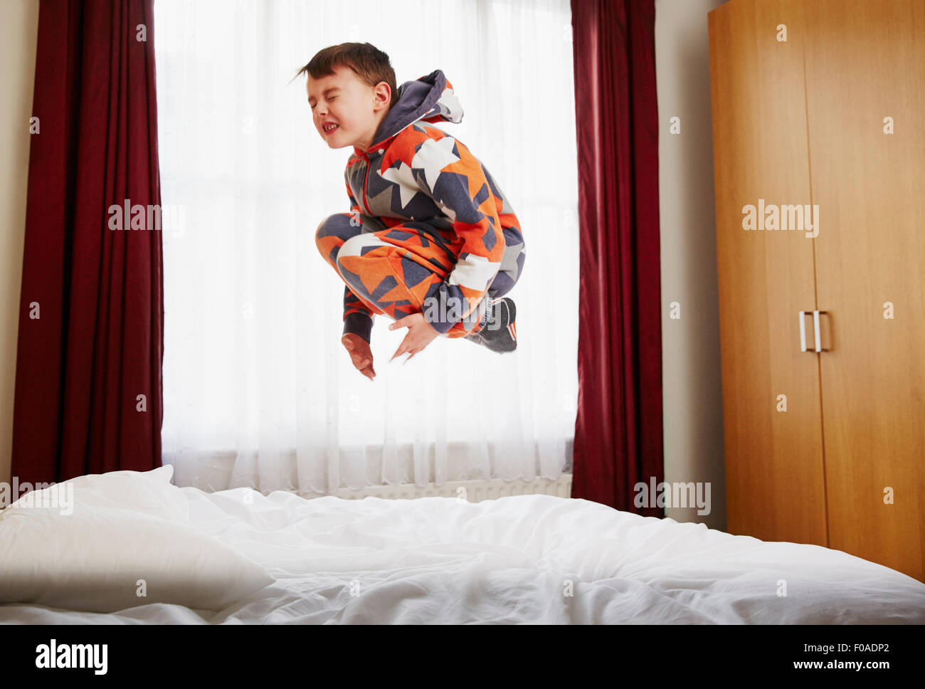Young boy jumping on bed Banque D'Images