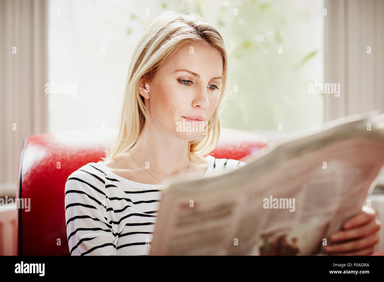 Mid adult woman reading newspaper Photo Stock