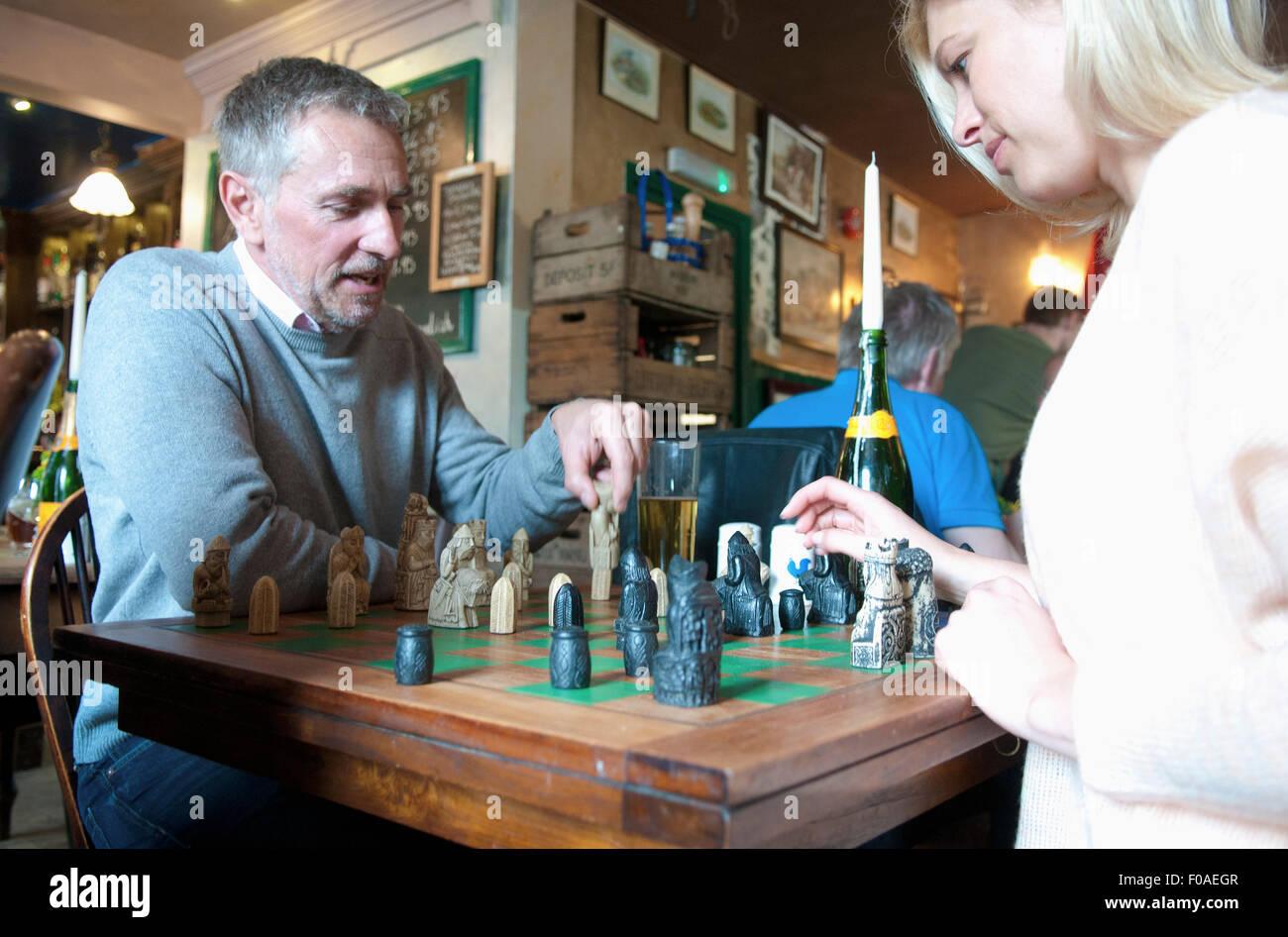 Couple jouant aux échecs dans un pub Banque D'Images
