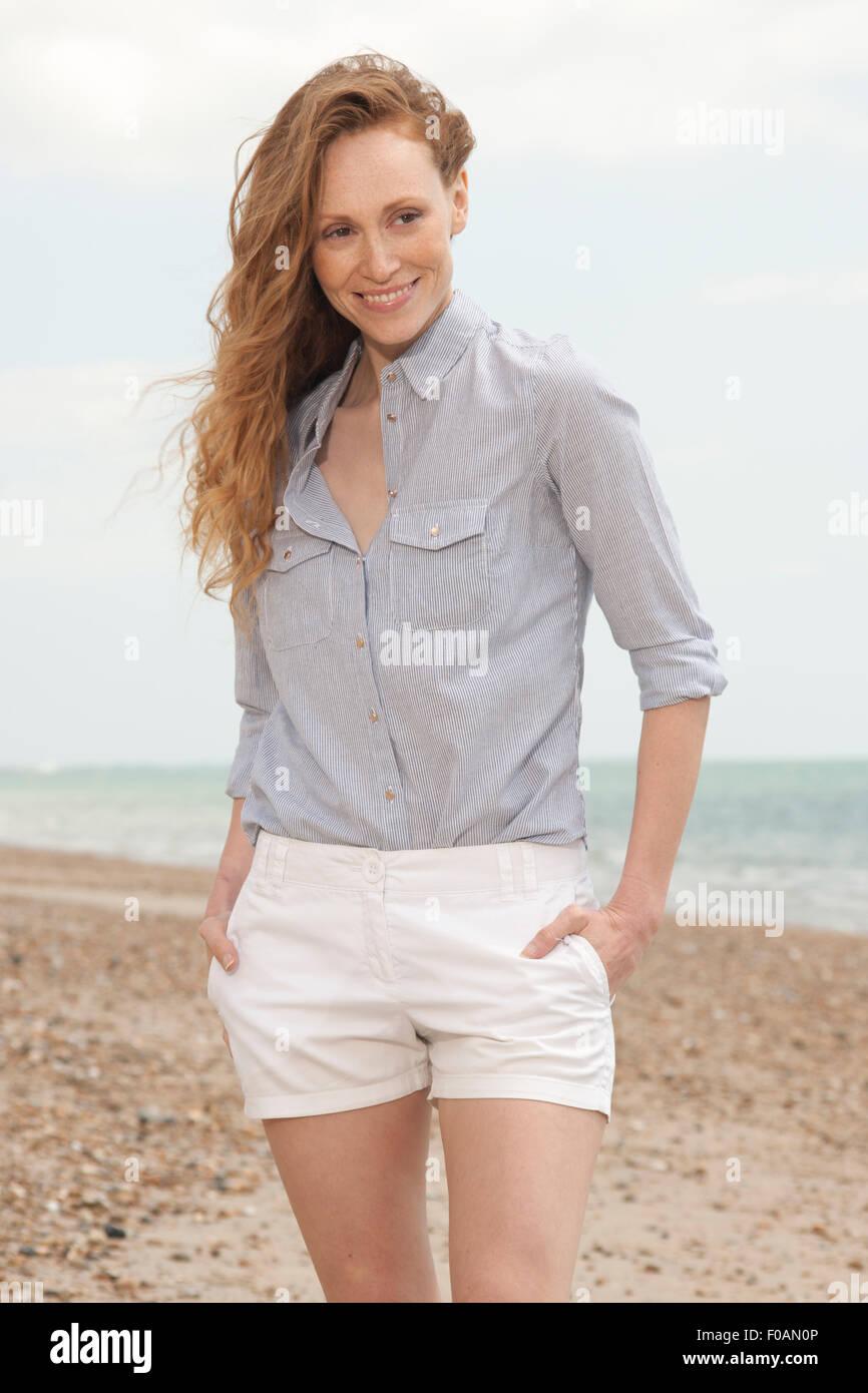 la réputation d'abord classcic parcourir les dernières collections Jolie rousse femme marchant le long de la plage en short et ...