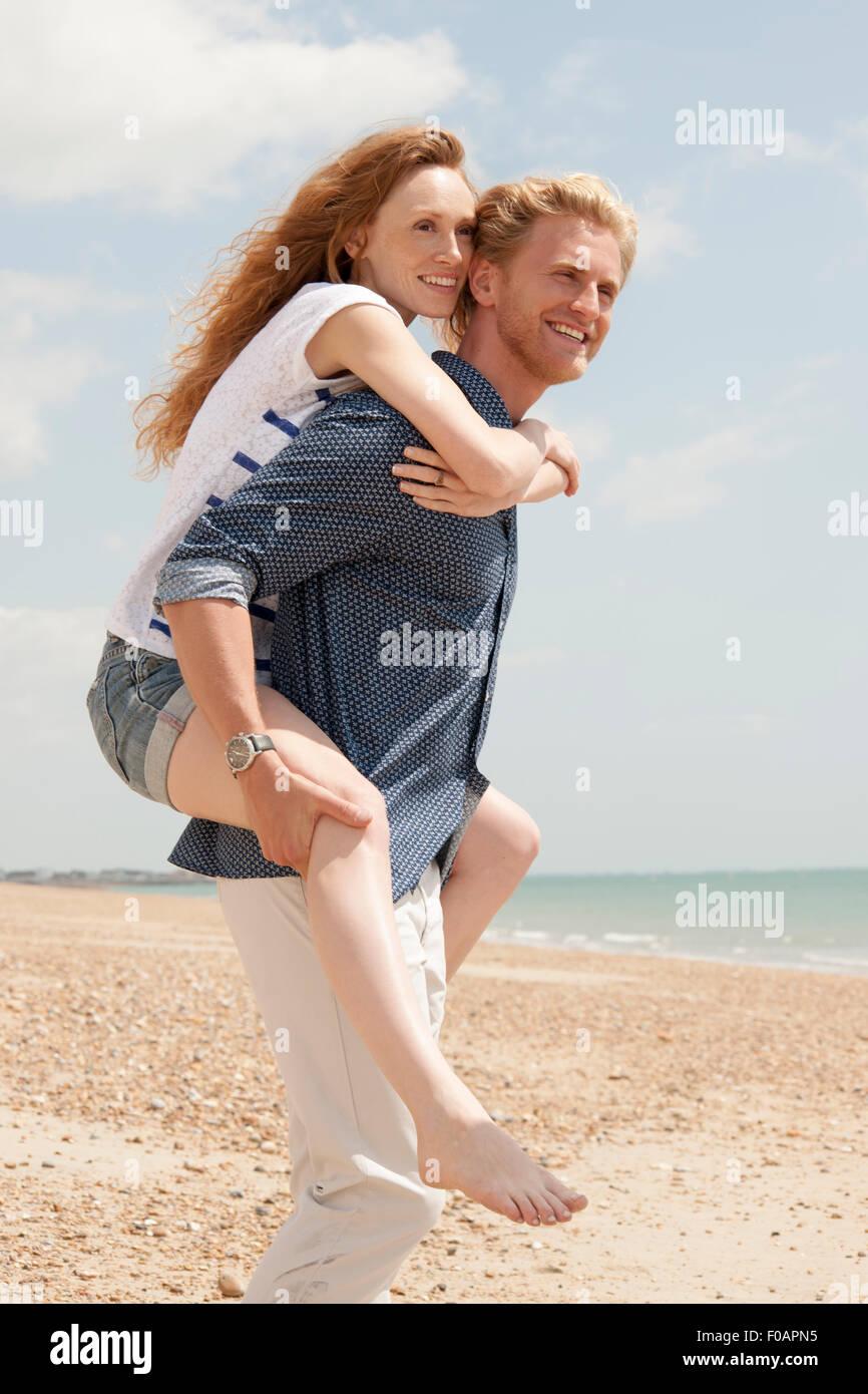 Man giving girlfriend piggyback un à la plage Photo Stock