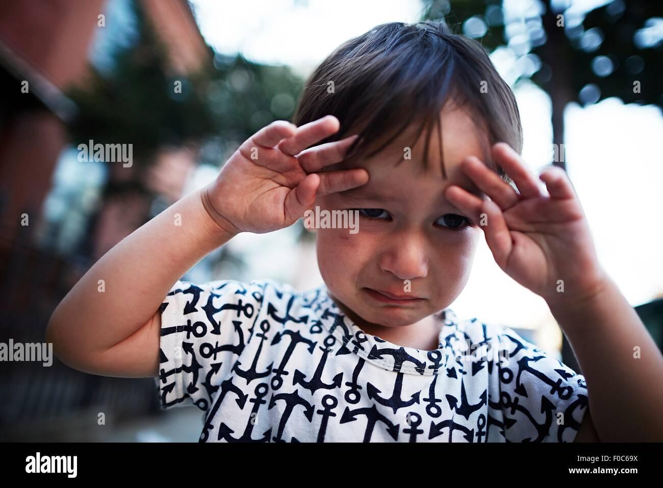 Portrait of boy crying on street Photo Stock