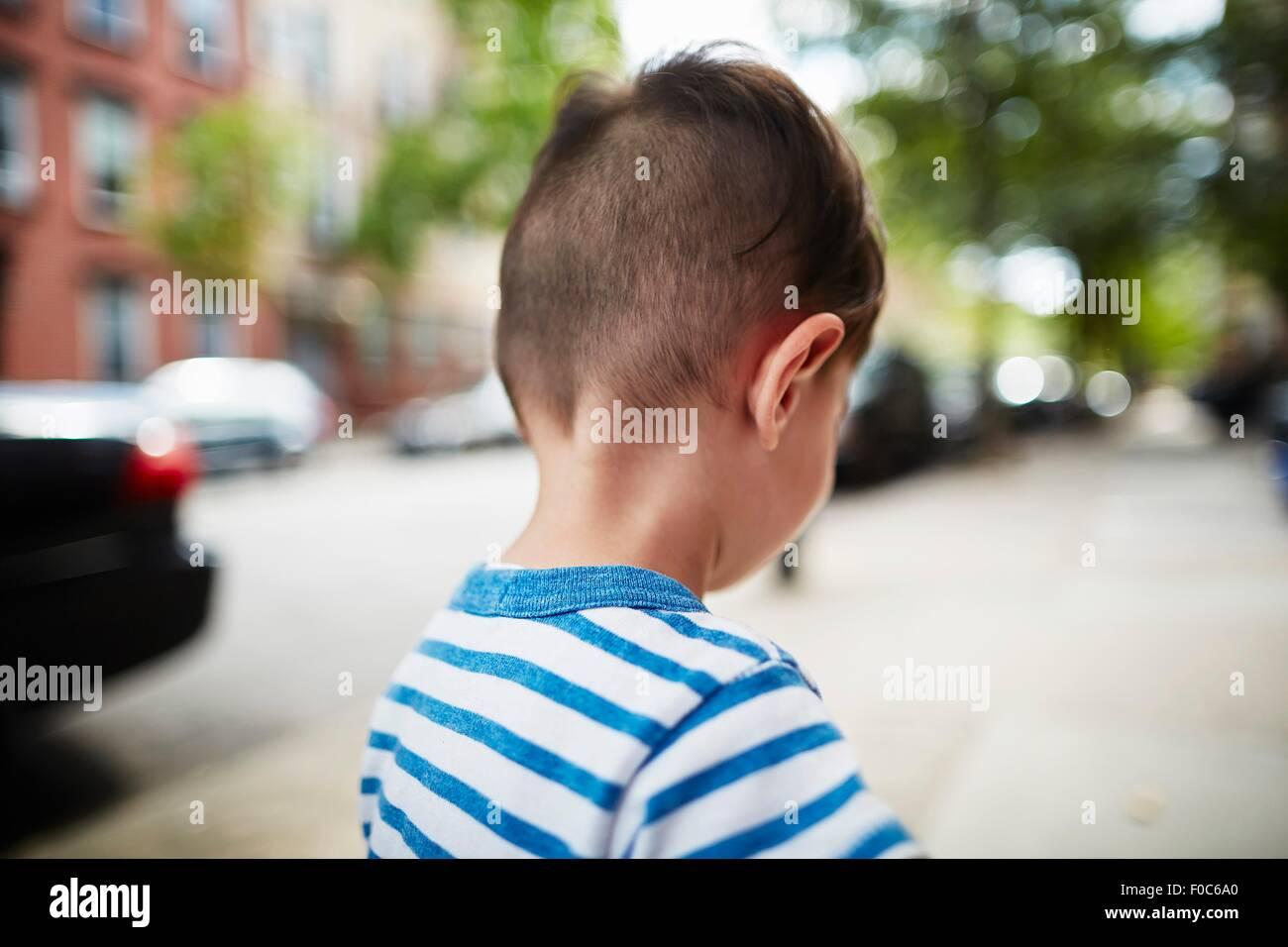 Vue arrière de boy walking down street Photo Stock