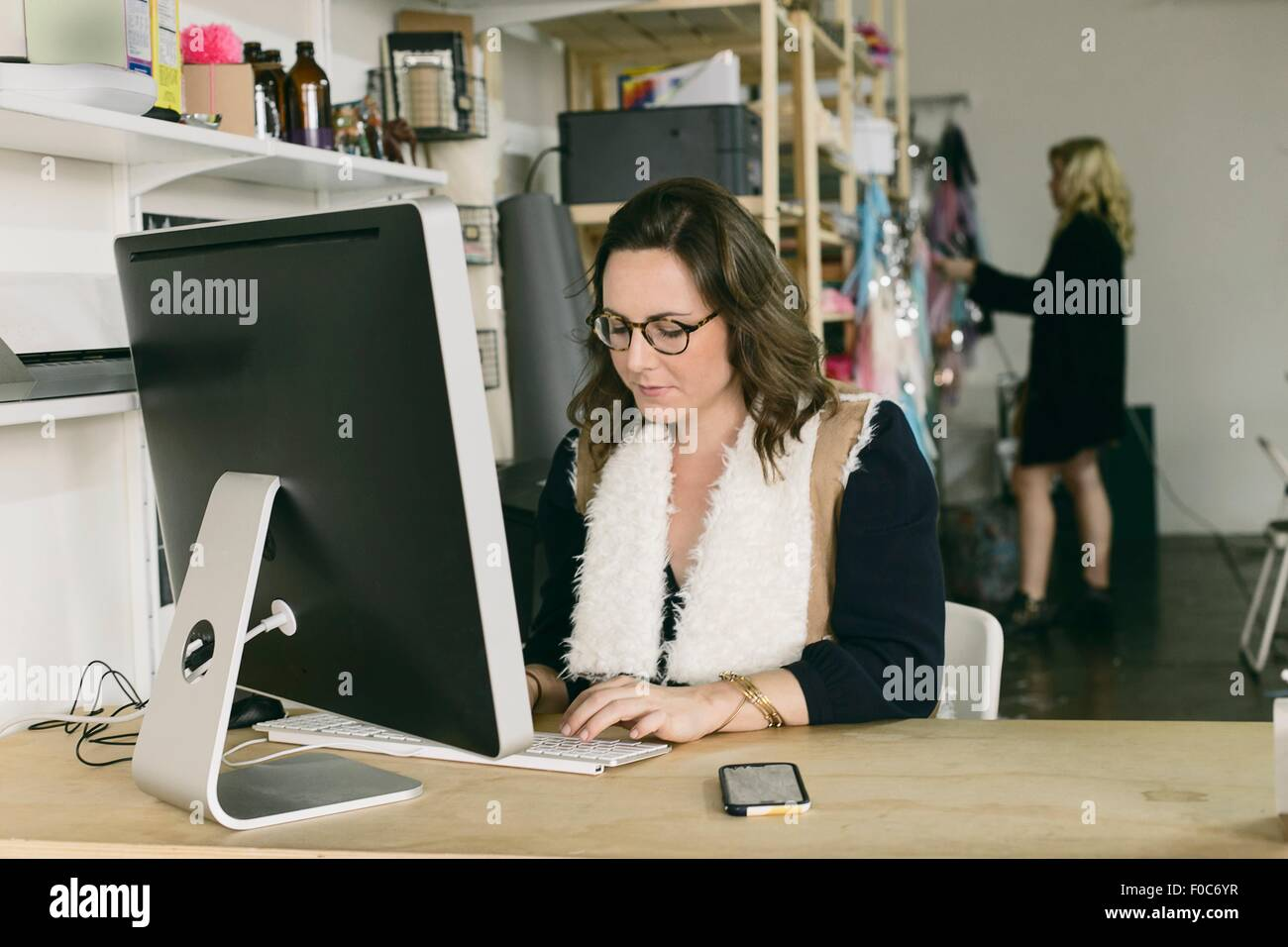 Female office worker at desk in design studio Photo Stock