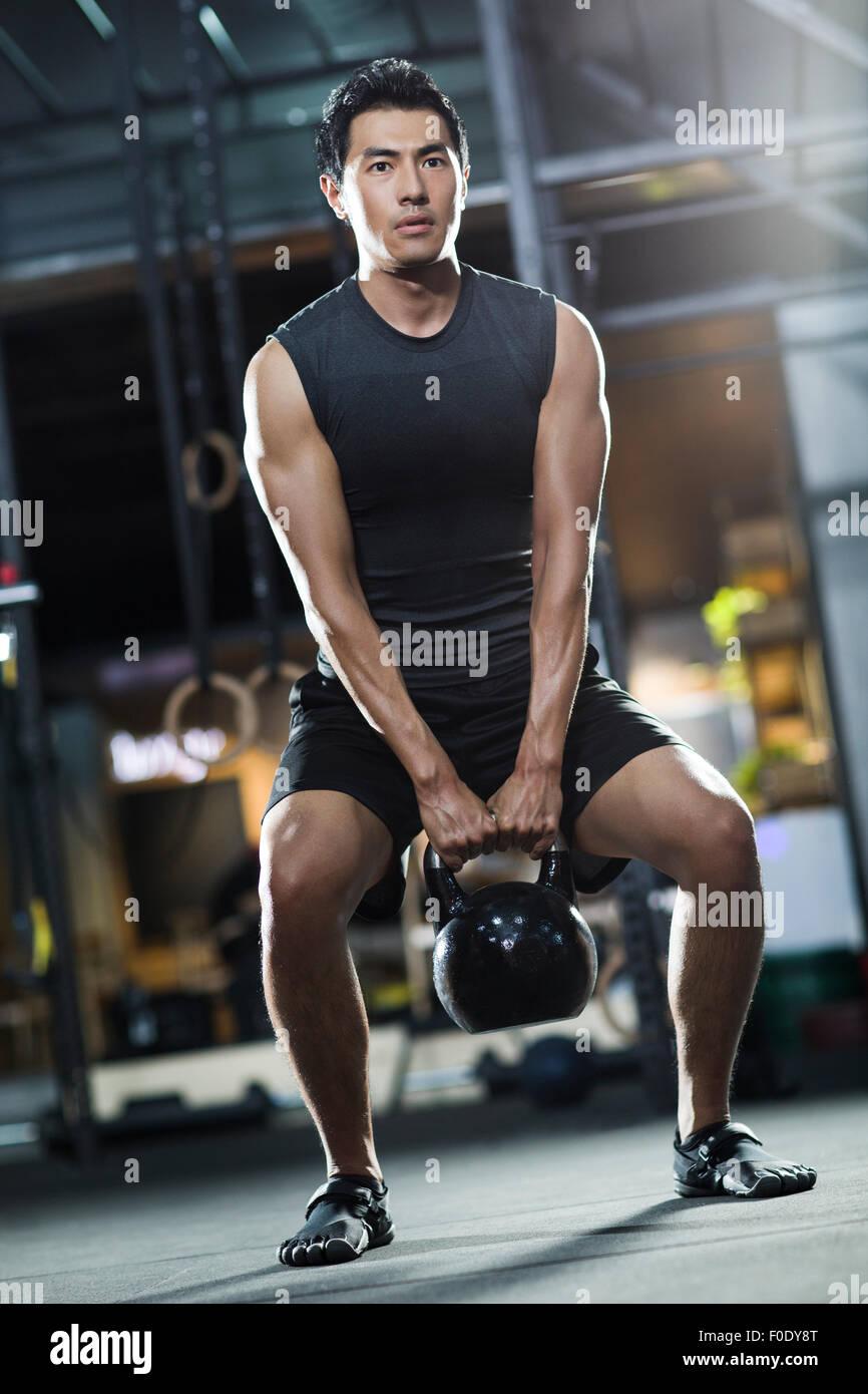 Jeune homme en formation avec kettlebell sport crossfit Photo Stock