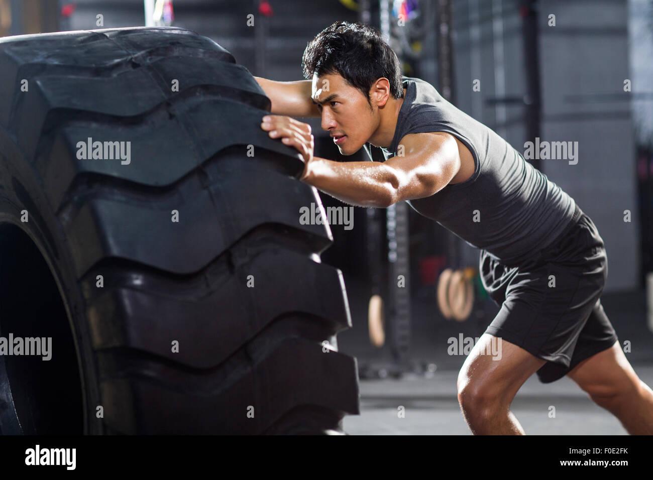 Jeune homme poussant en grand pneu sport crossfit Photo Stock