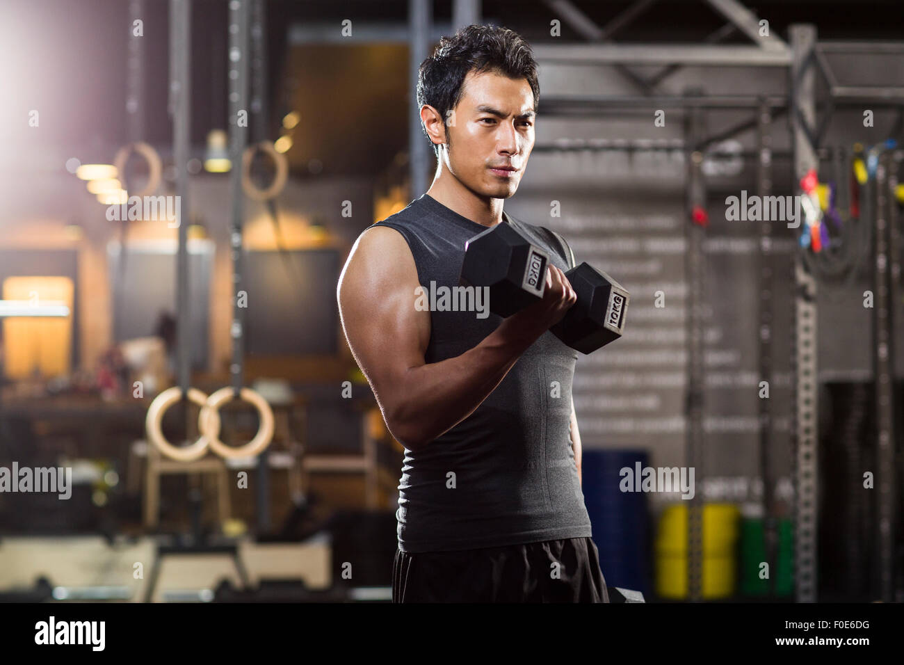Young man lifting weights at gym Photo Stock