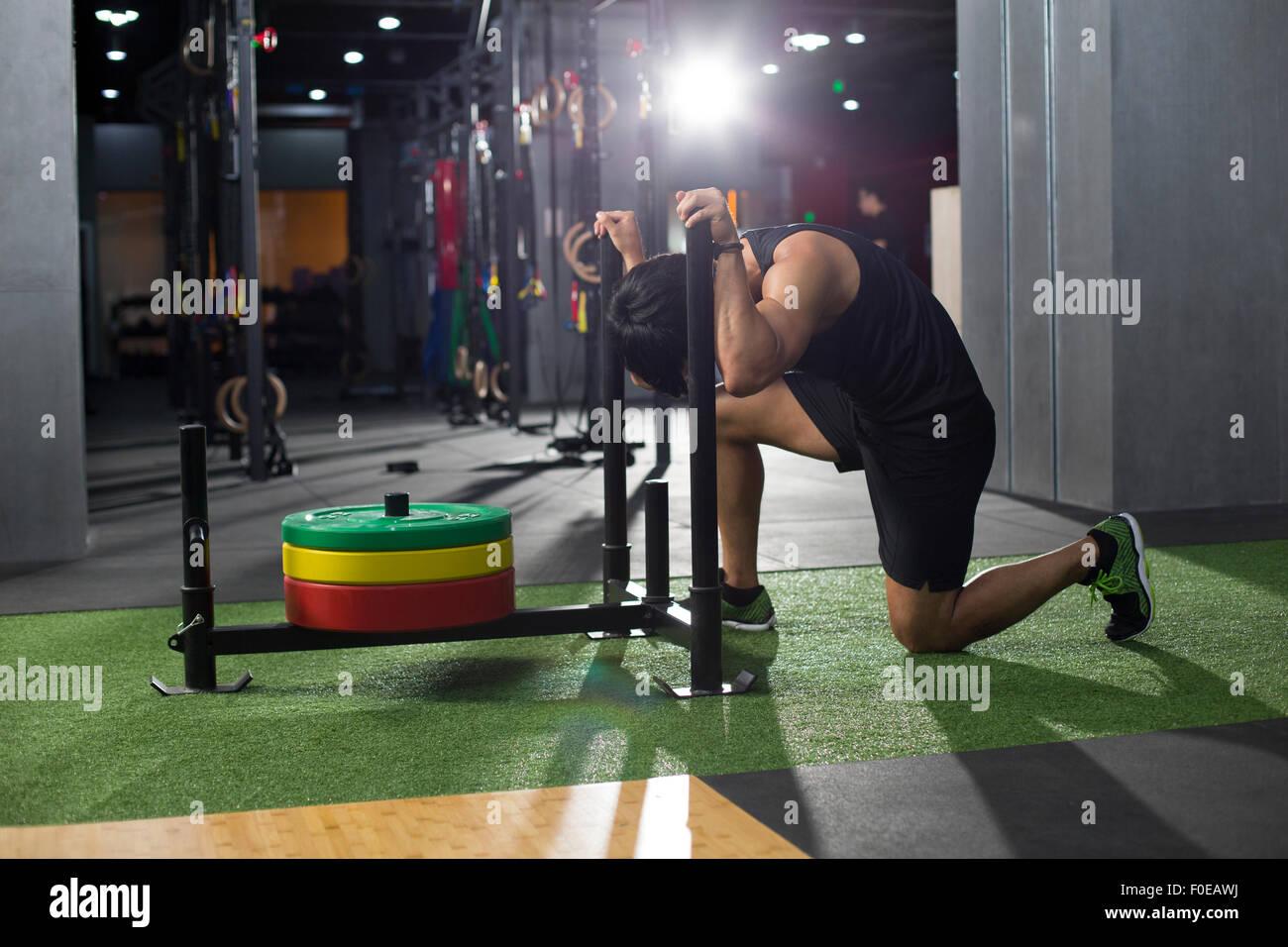 Jeune homme poids poussant à traîneau sport Photo Stock