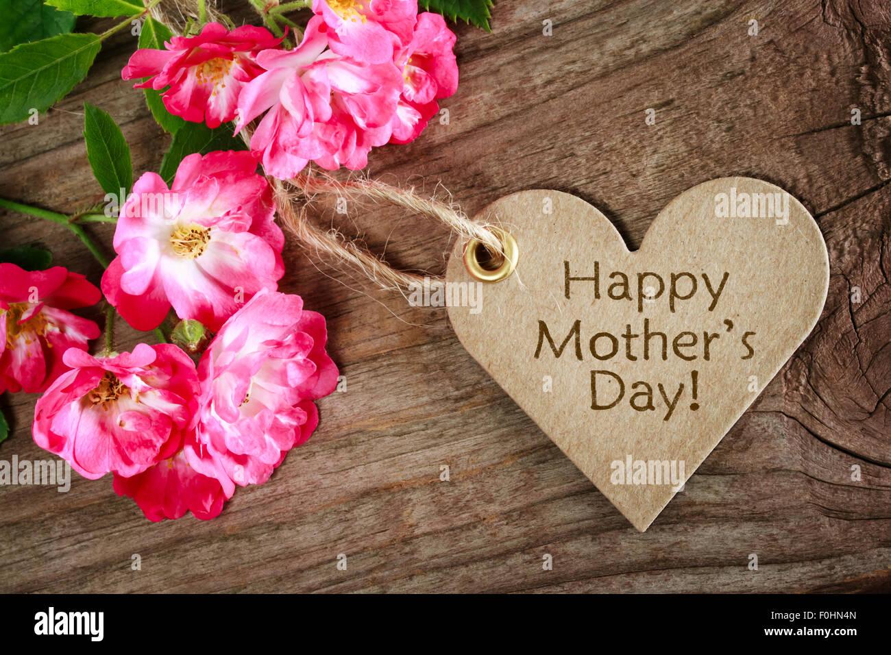 Carte de fête des mères en forme de coeur avec des roses sur fond de bois Photo Stock