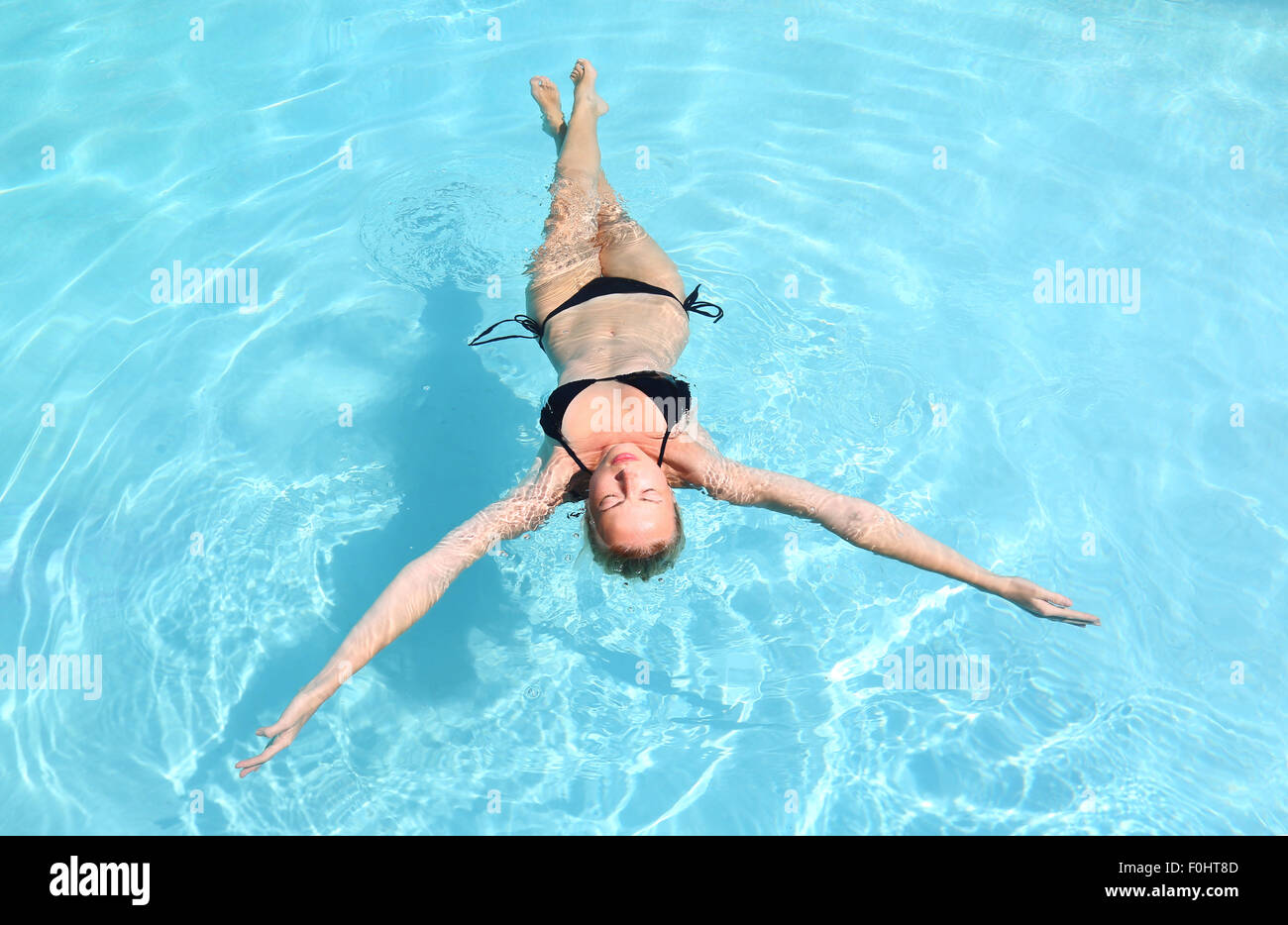 Dame de race blanche flottant dans la piscine. Photo Stock