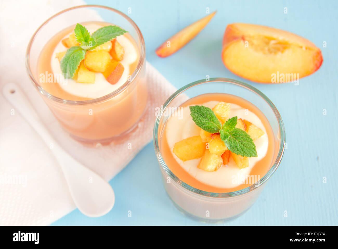 Smoothie pêche dessert (mousse) avec du yaourt et de la menthe en partie verres Photo Stock