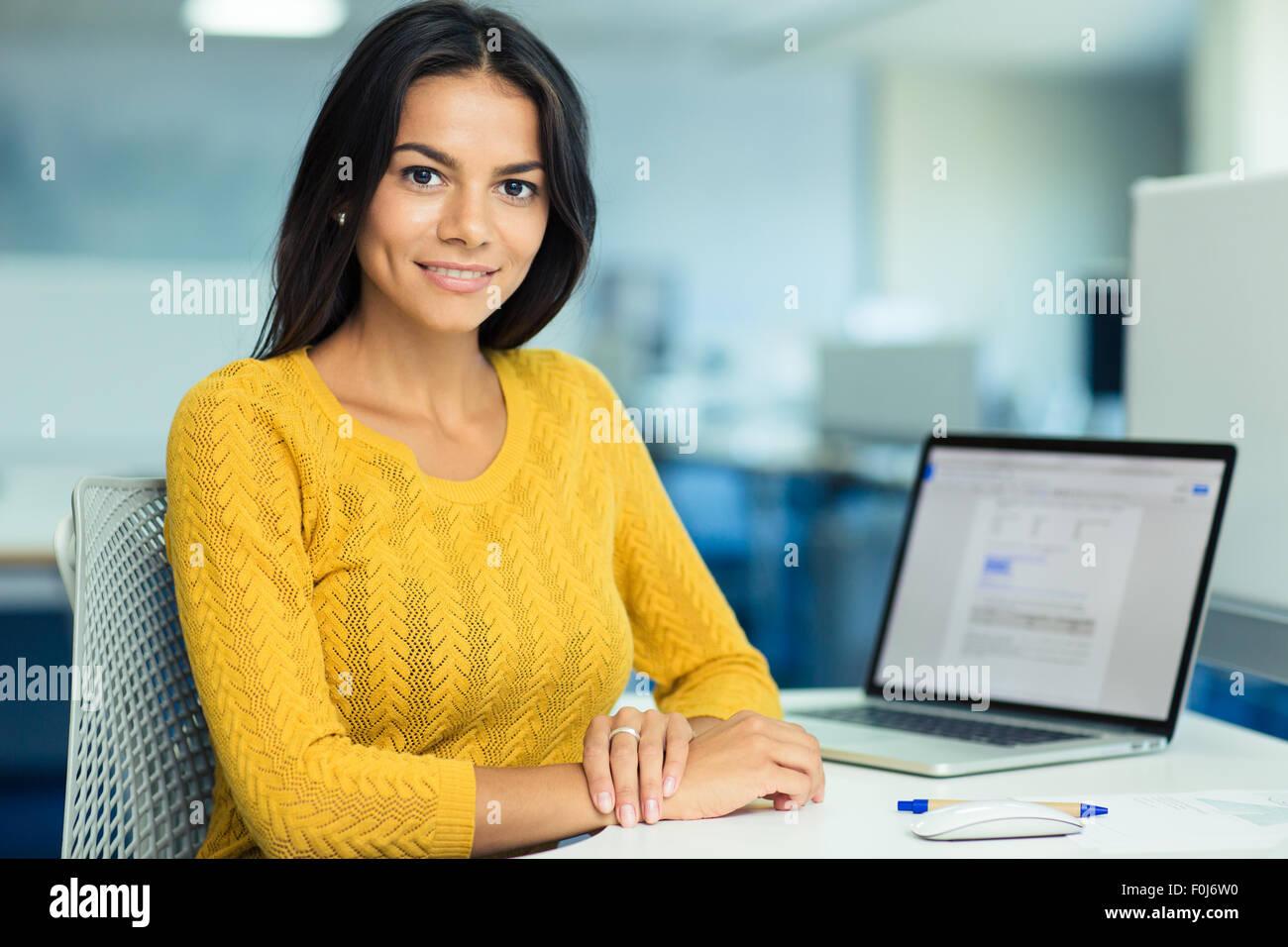 Portrait of a happy casual businesswoman in sweater assise à son bureau en milieu de travail Photo Stock