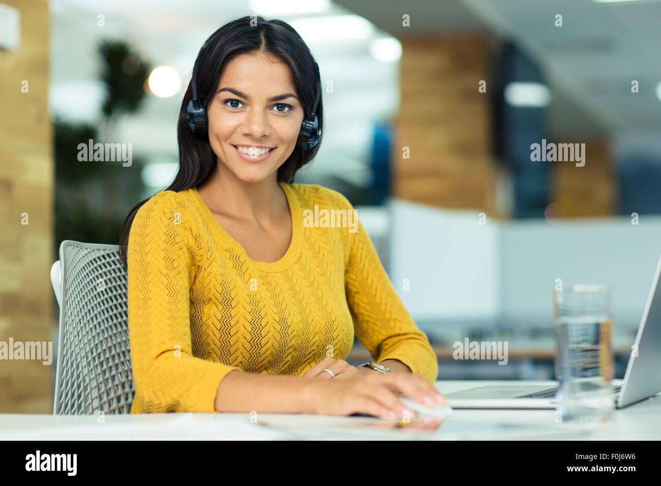 Portrait of a cheerful businesswoman in headphones assise à son bureau en milieu de travail et looking at camera Banque D'Images