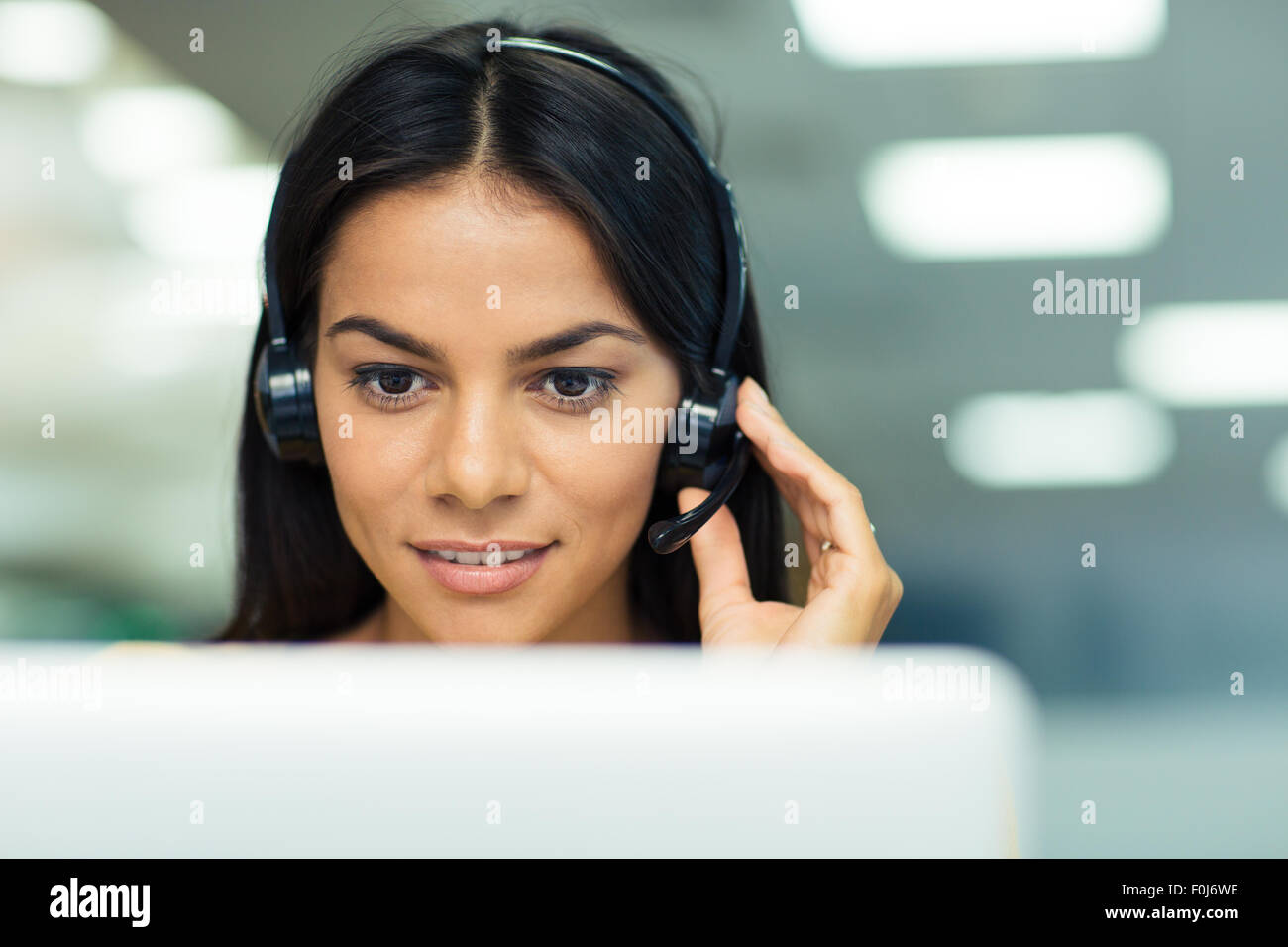 Happy businesswoman working on laptop with headphones in office Banque D'Images