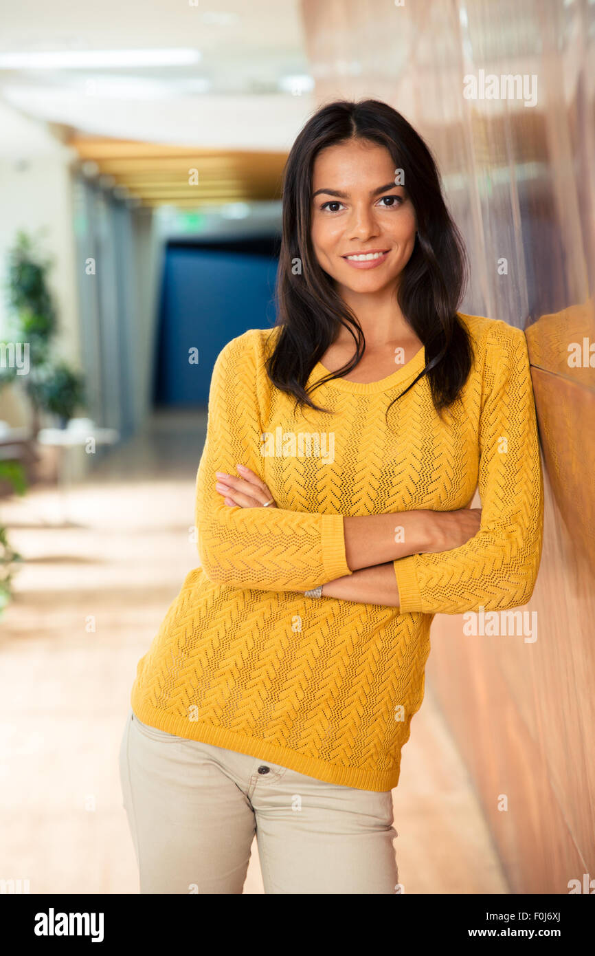 Portrait of a smiling casual businesswoman standing with arms folded in office Photo Stock