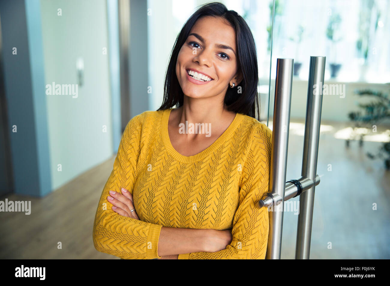 Portrait of a cheerful casual businesswoman standing with arms folded in office Photo Stock