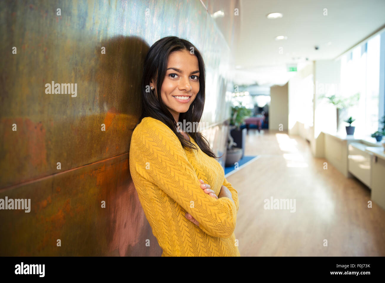 Portrait of a smiling Pretty woman with arms folded in hallway Photo Stock