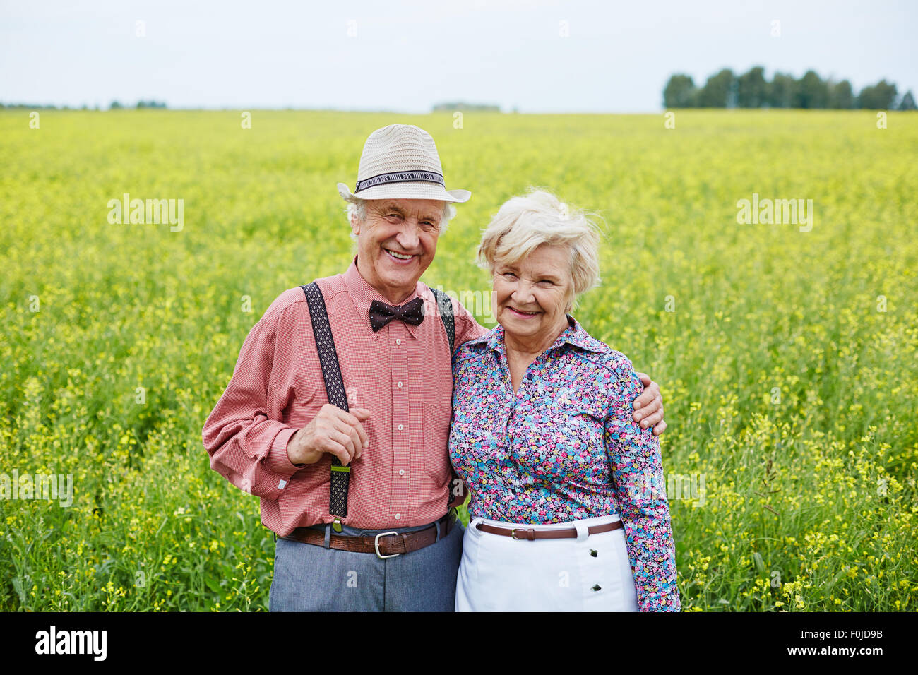 Les personnes âgées gaies looking at camera en zone rurale Photo Stock