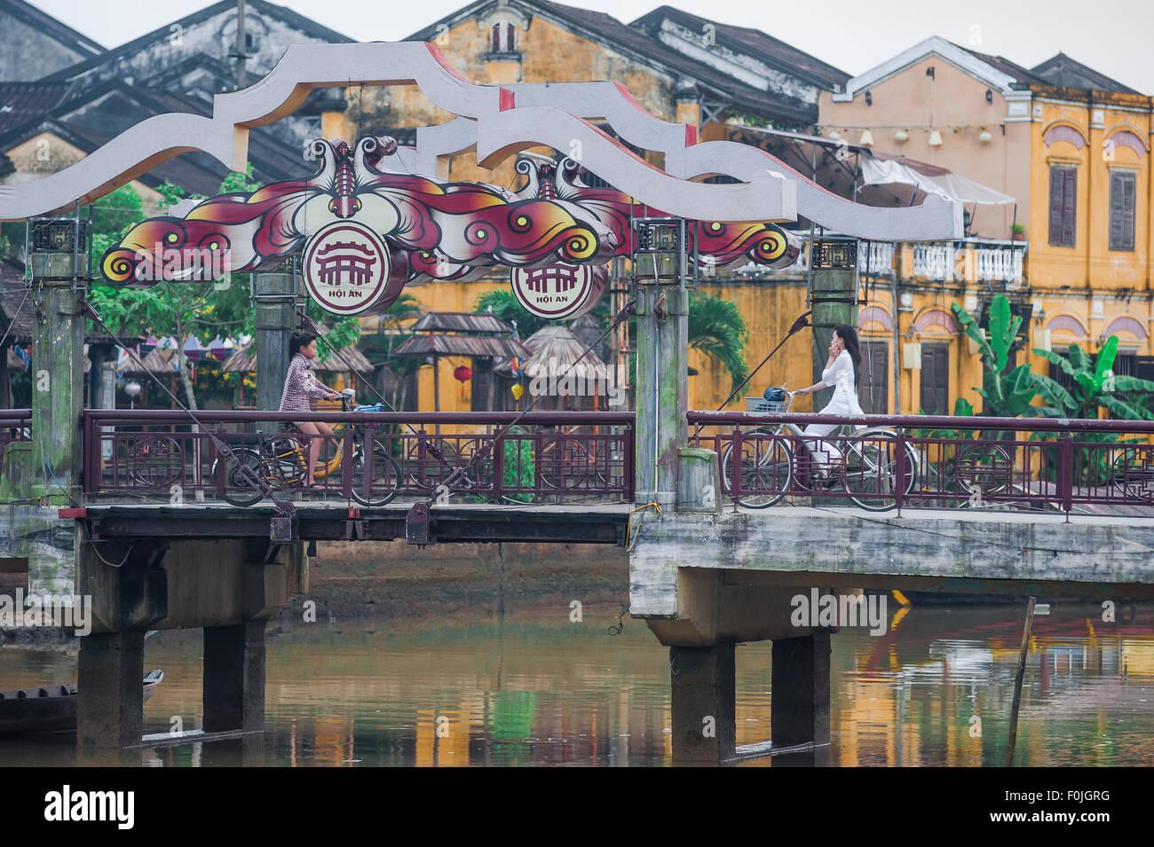 Hoi An bridge centre, juste après l'aube cyclistes utiliser la passerelle qui enjambe la rivière Thu Photo Stock