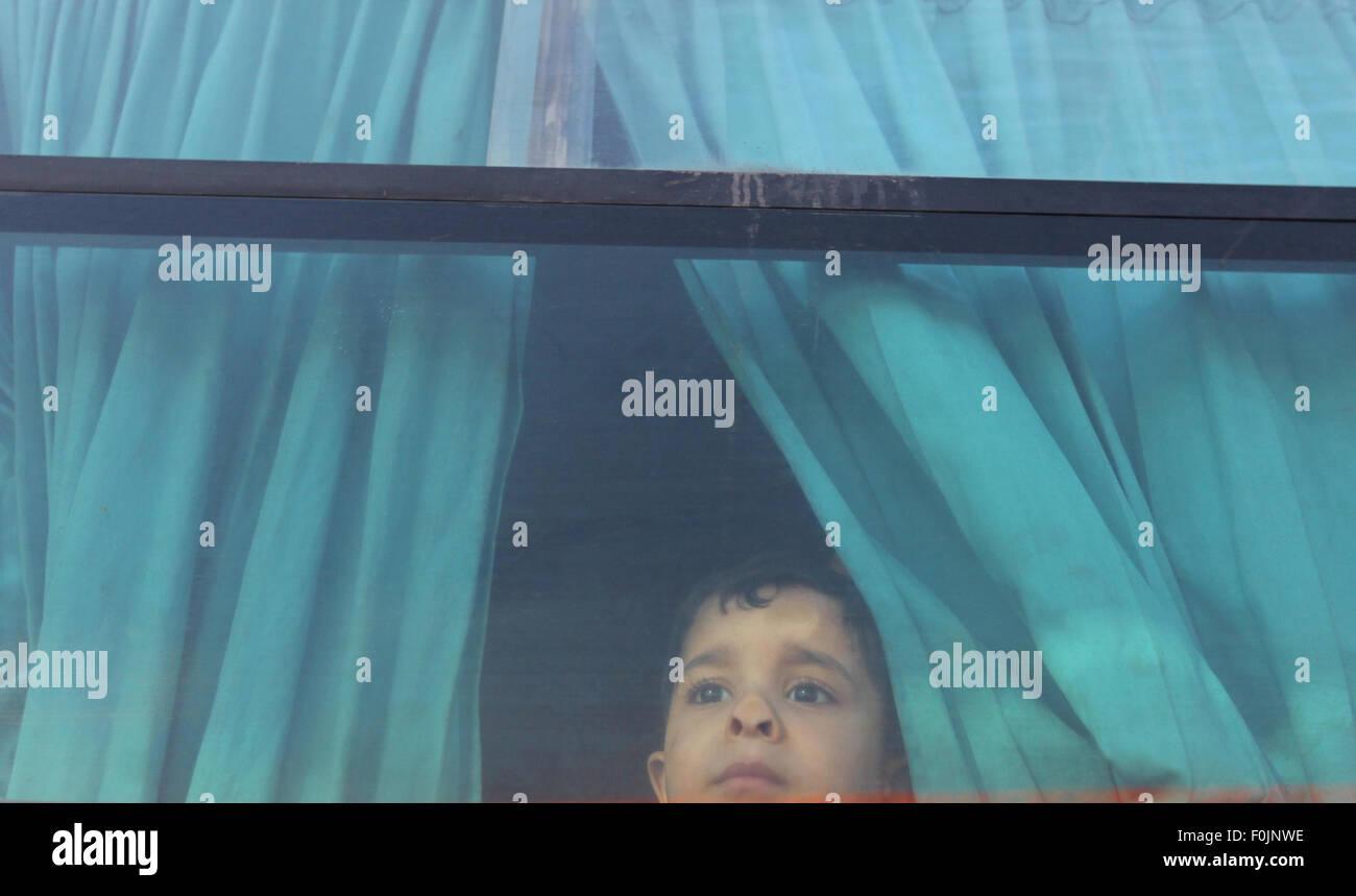 Rafah, bande de Gaza, territoire palestinien. Août 17, 2015. Un garçon palestinien assis dans un bus réagit Photo Stock