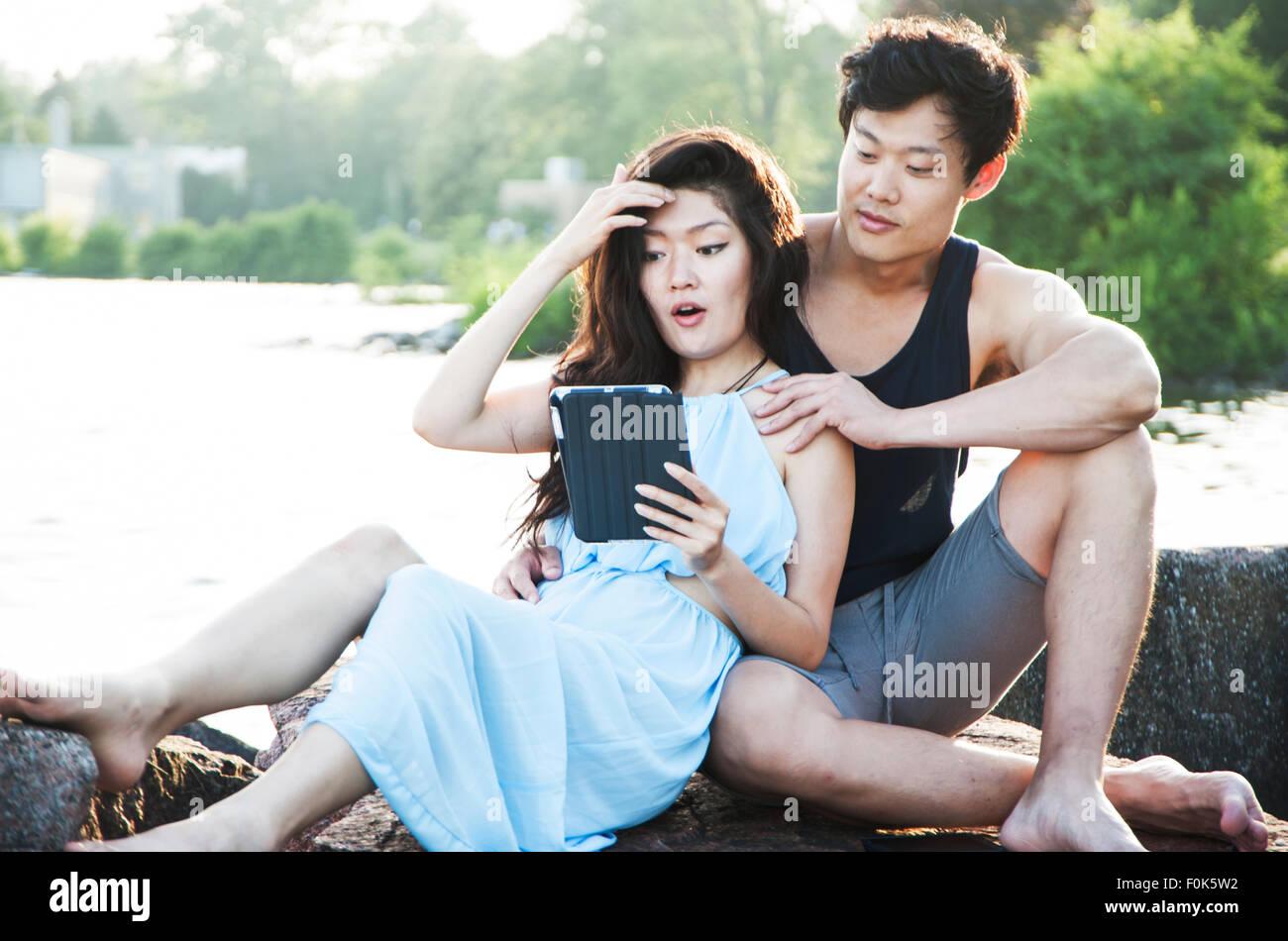 Asian couple assis dehors avec femme de lire un e-reader Photo Stock