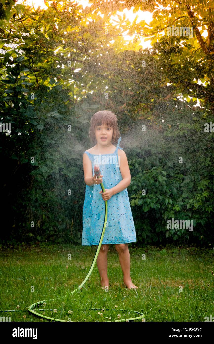 Petite fille avec tuyau de jardin Banque D'Images