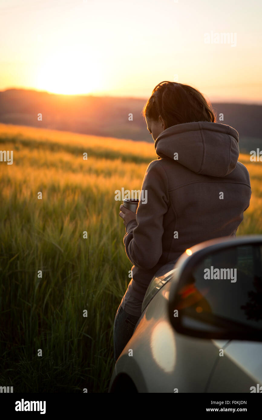 Allemagne, woman leaning on voiture en face d'un champ au lever du soleil Photo Stock