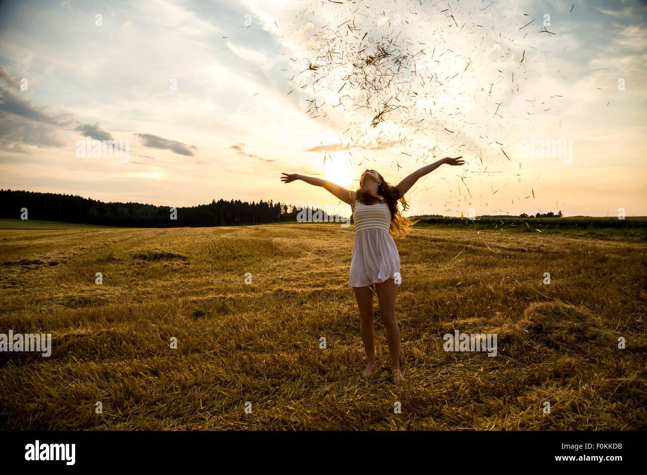 Jeune femme debout sur champ d'orge, de jeter de la paille Photo Stock