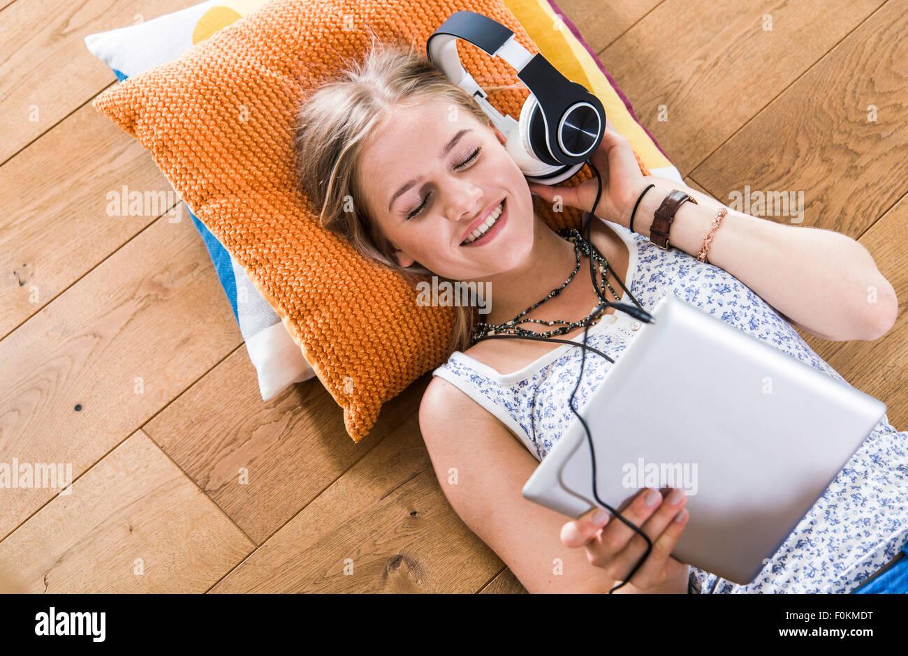 Teenage girl lying on floor écouter de la musique à partir de la tablette numérique Photo Stock
