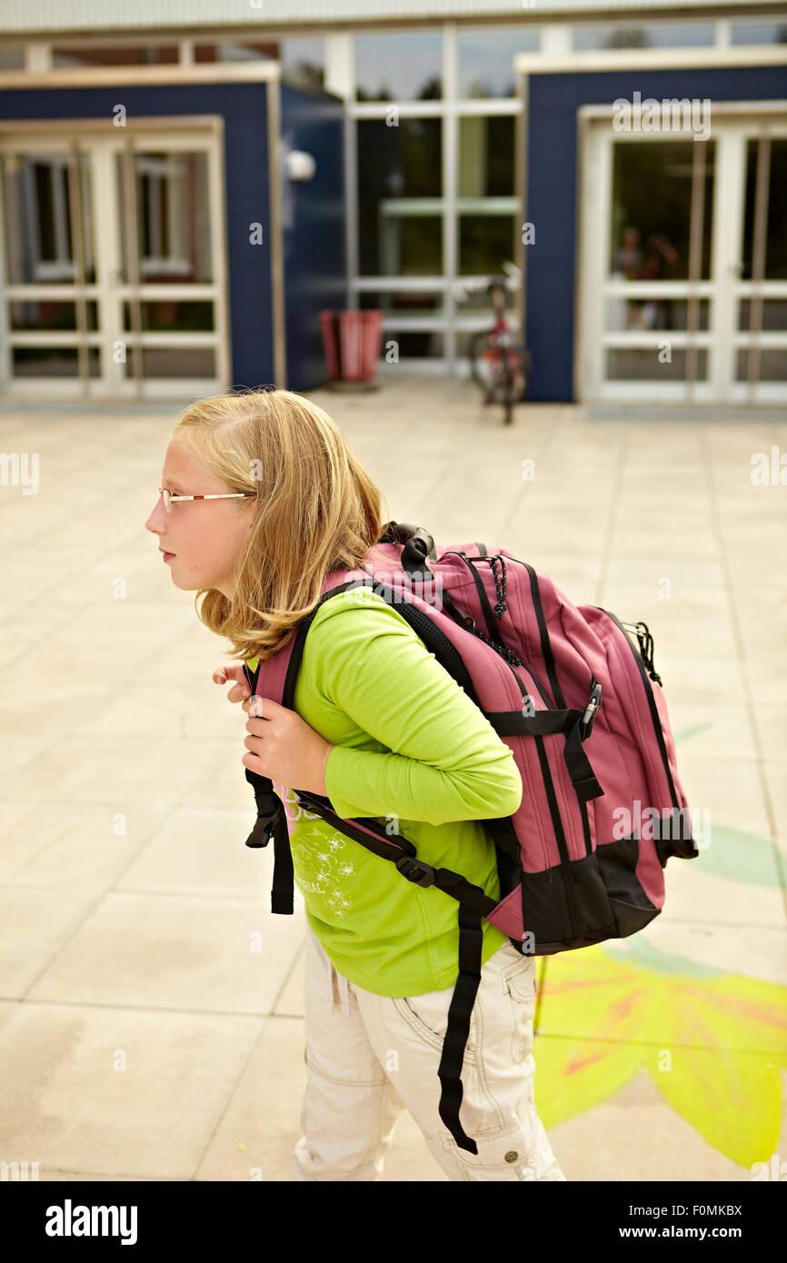 Avec un lourd sac d'écolière Photo Stock