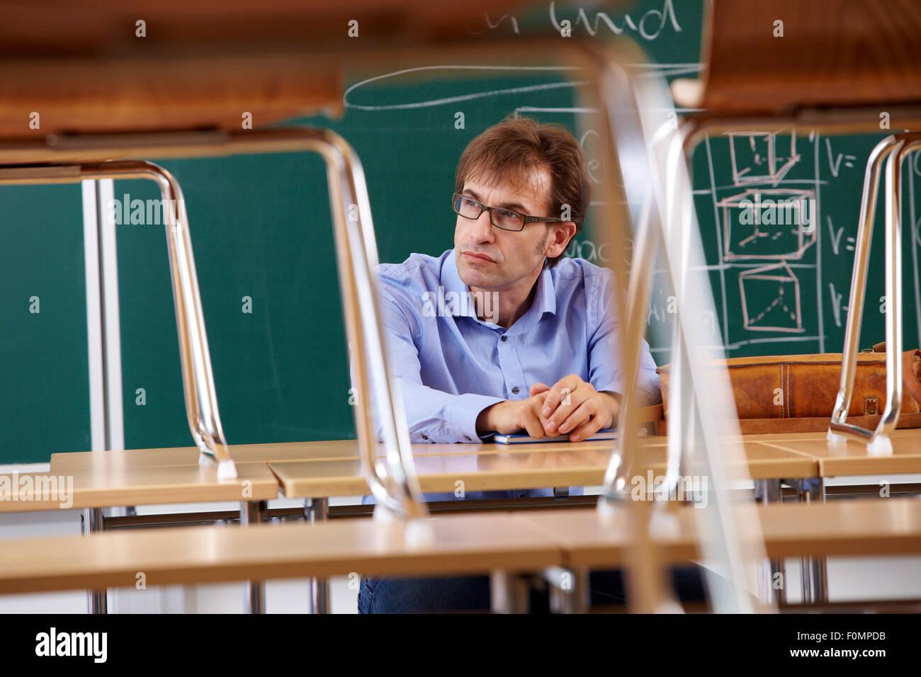 Épuisé enseignant en salle de classe Photo Stock