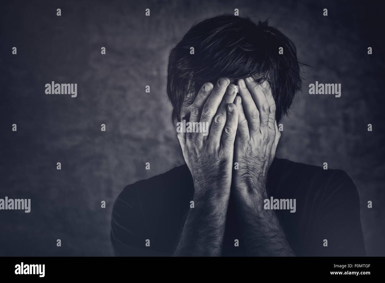 Le chagrin, l'homme qui couvre le visage et de pleurer, image monochromatique Photo Stock