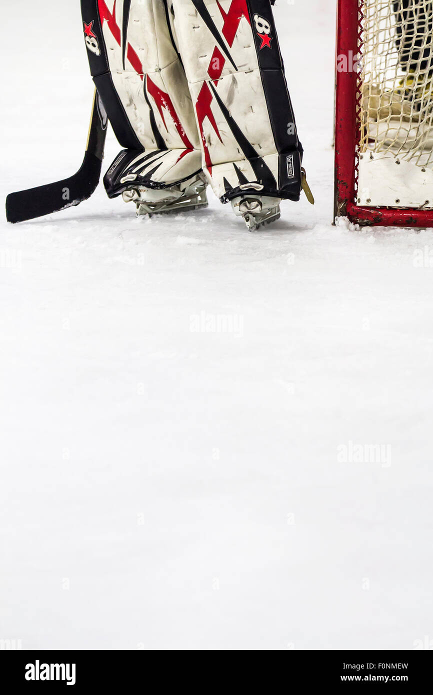 Gardien de but de hockey sur glace se tenait à côté de l'objectif sur la glace. Photo Stock