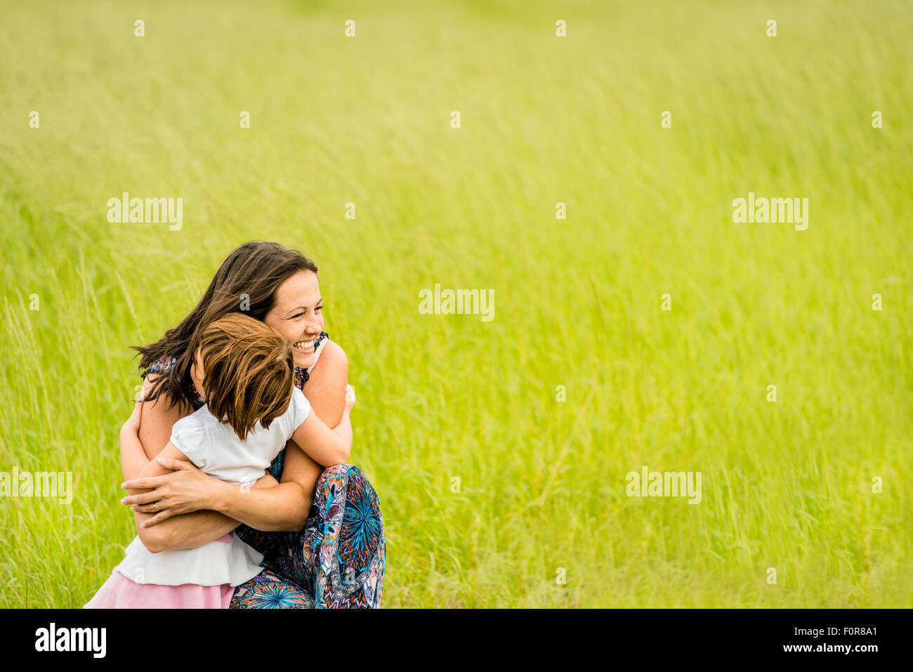 La mère et l'enfant sont hugging et faire place au dehors, dans la nature Photo Stock