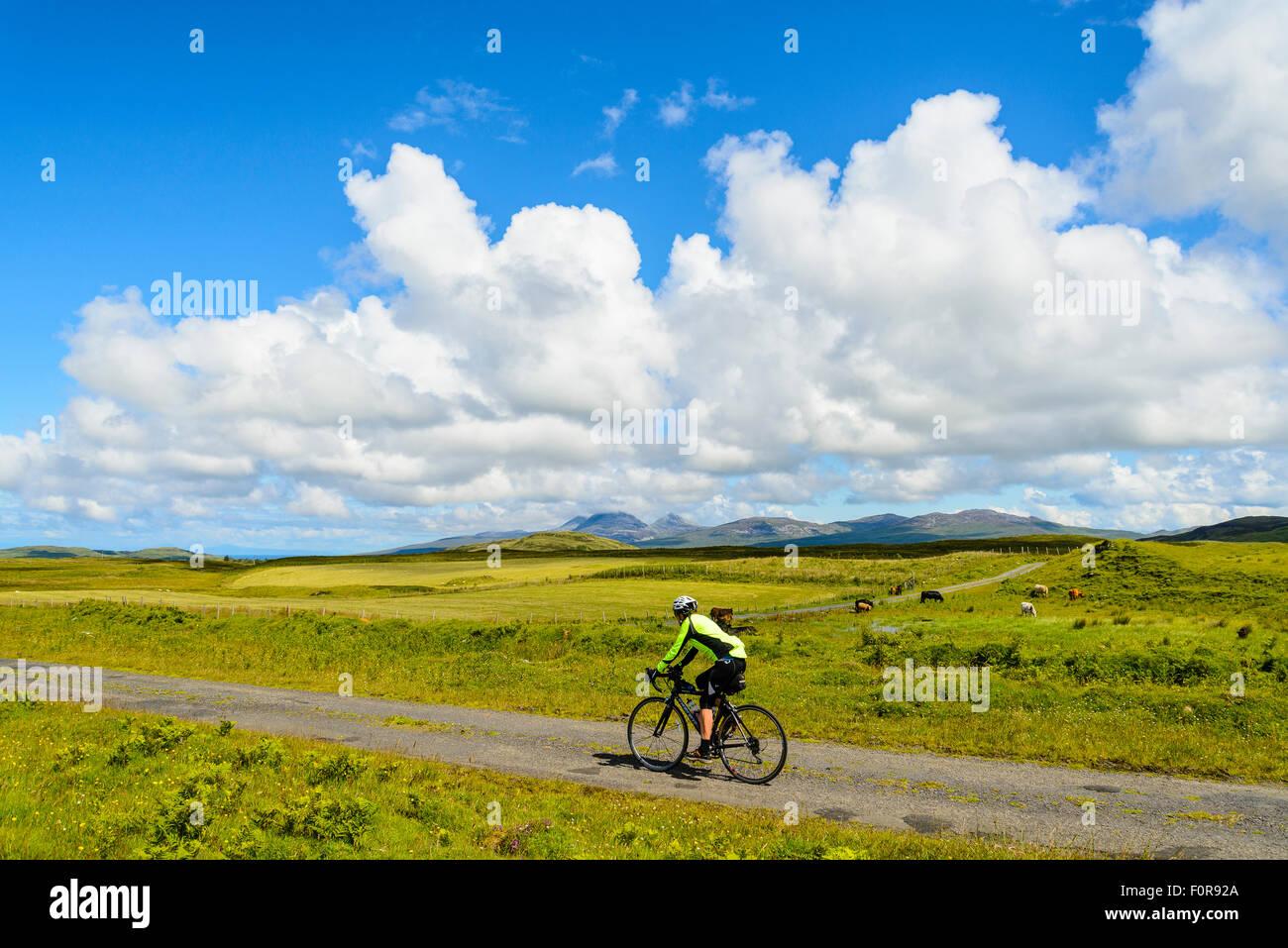 Cycliste féminine sur route vide sur l'île d'Islay en Écosse à la recherche de la Paps of Jura Banque D'Images