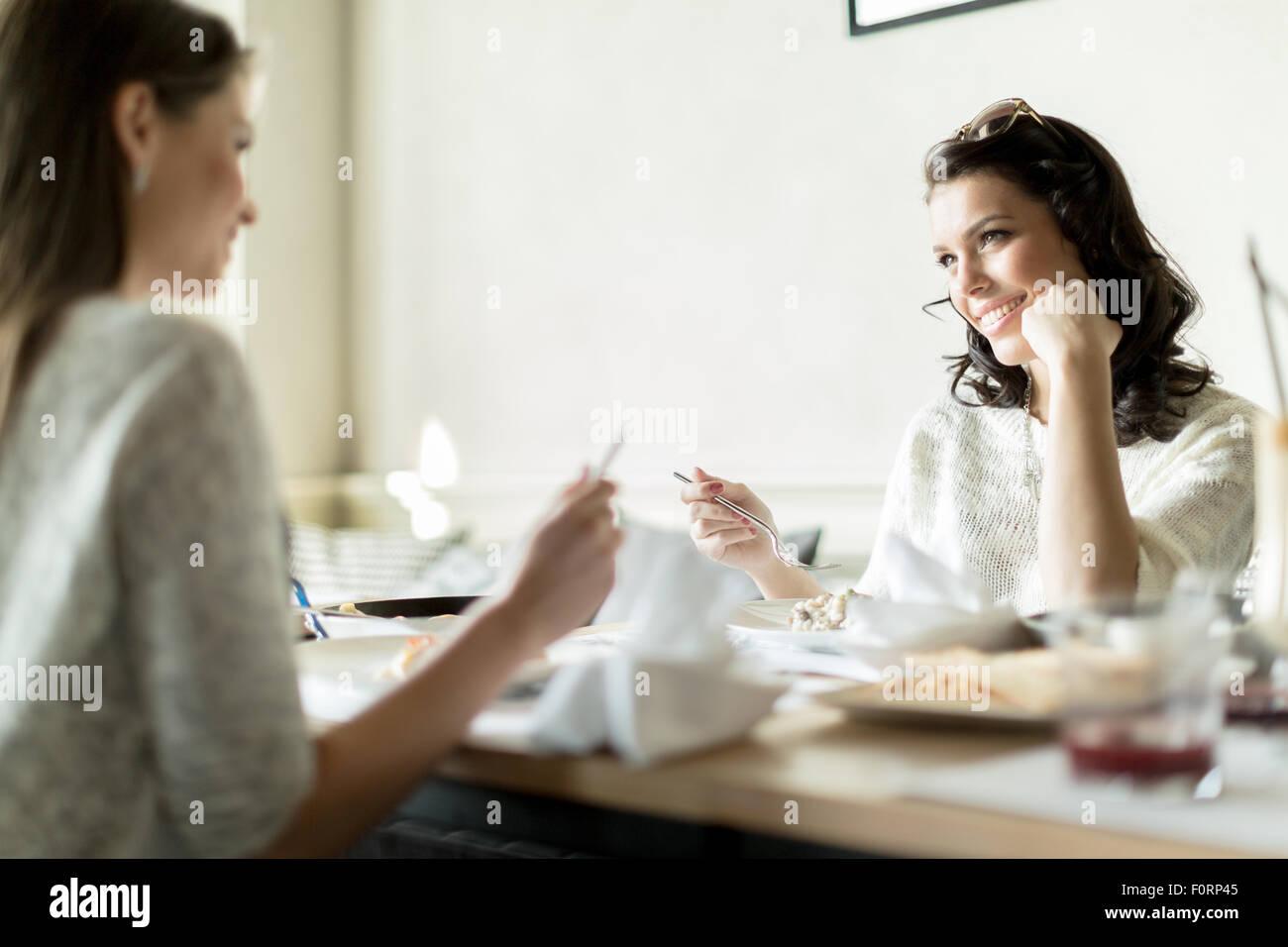 Deux gorgeaus mesdames manger dans un restaurant tout en ayant une conversation Photo Stock