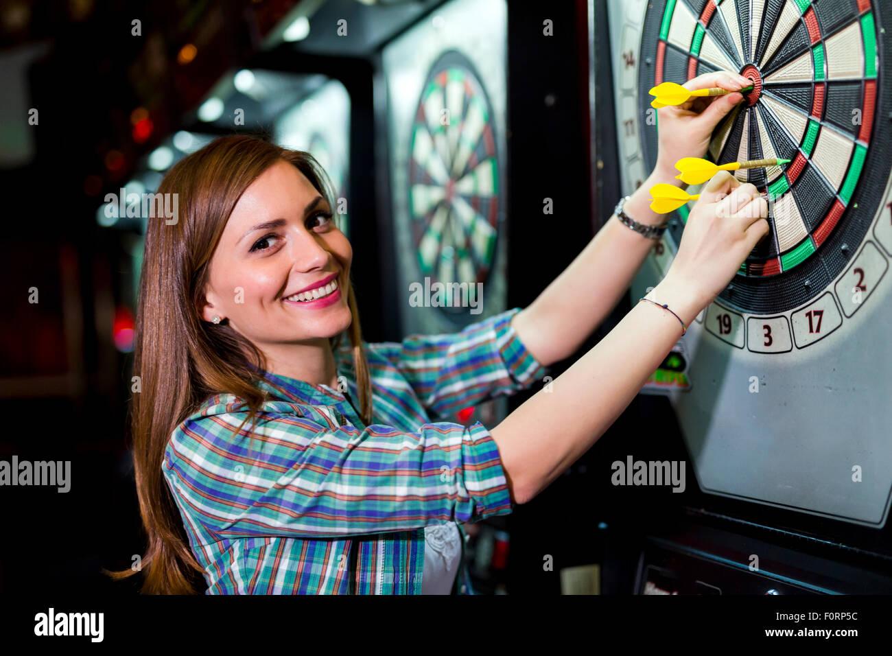 Belle Jeune femme jouant aux fléchettes dans un club et smiling Photo Stock