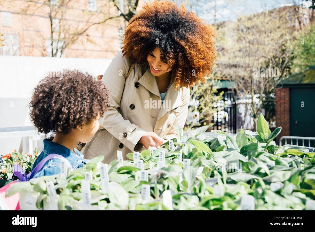 Mère et fille à la recherche de plantes pour vente Photo Stock