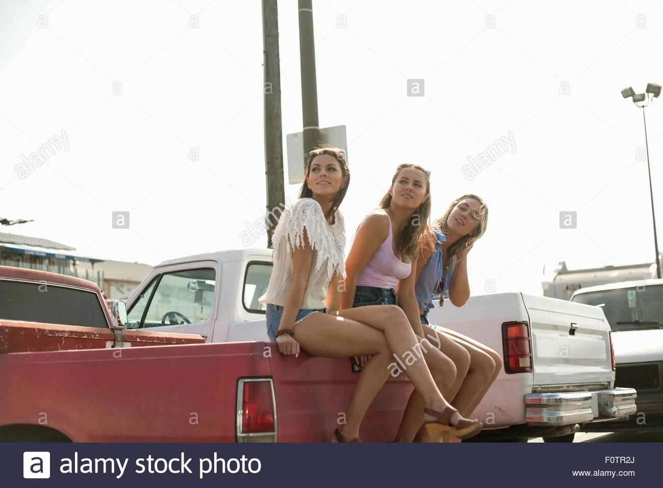 Trois jeunes femmes, assis à l'arrière du camion, à l'écart Photo Stock